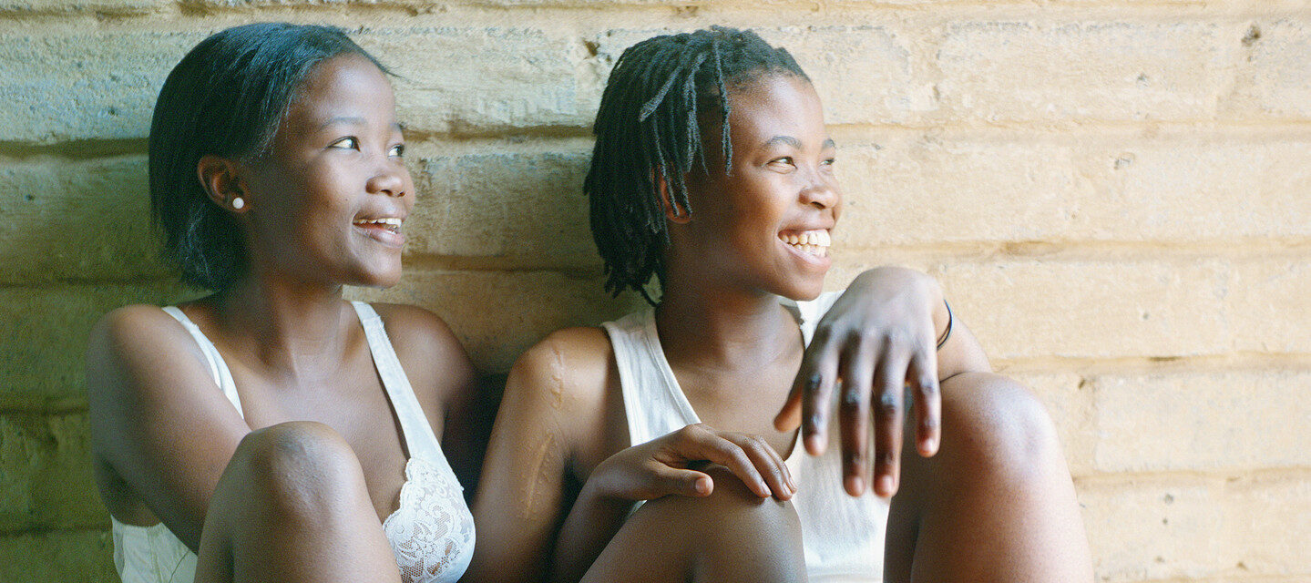 Two dark-skinned young women with short hair sit together against a white brick wall, their limbs lovingly intertwined and glowing smiles across their faces. One wears a white bra and shorts, and the other a white tank-top and blue shorts.