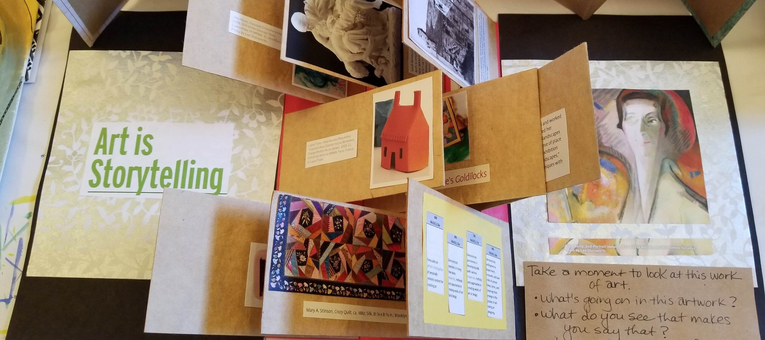 A birds-eyed view of a variety of artists books showing a variety of folded paper and works of art.