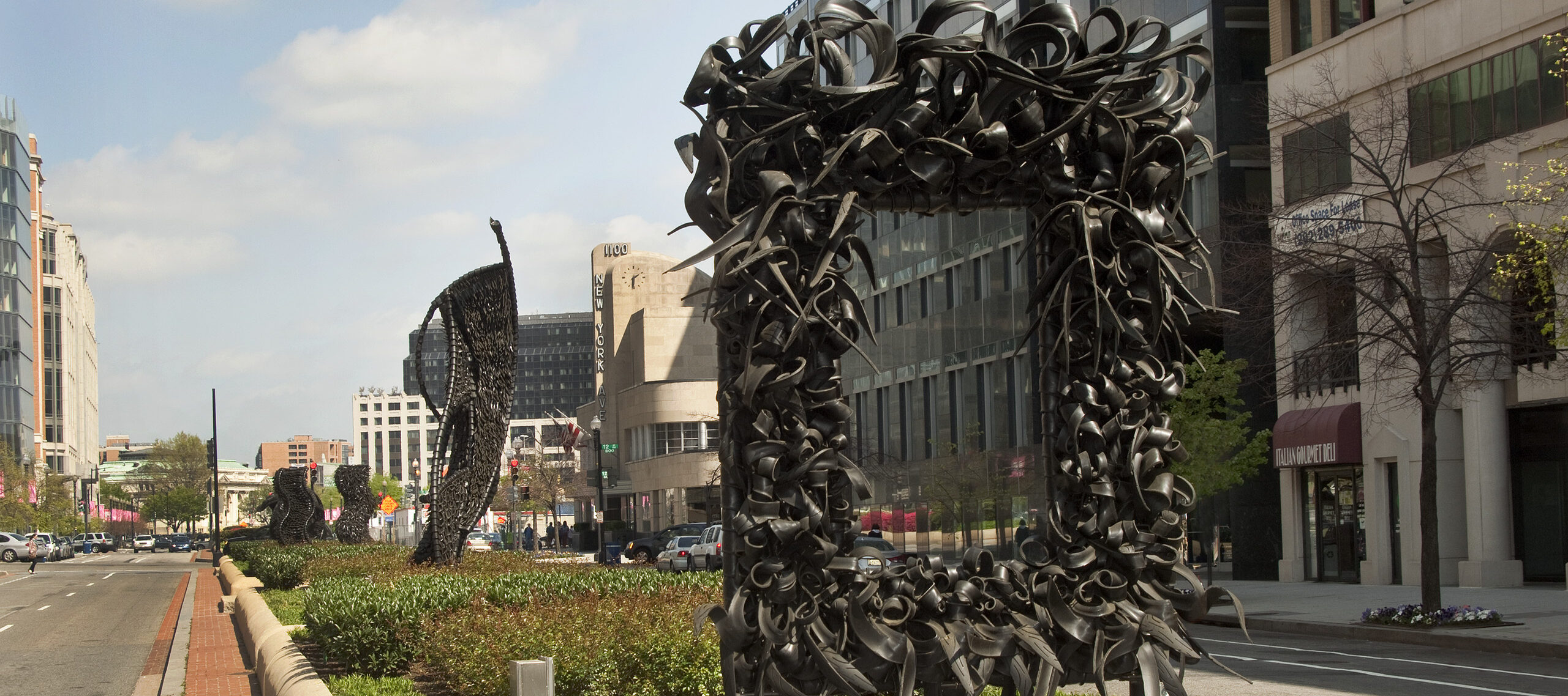 "A large metal sculpture stands in the middle of the street, similar to an empty rectangular picture frame. The ""frame"" is crowded with undulating, coiling metal sculptural elements that occasionally end in spikes. Behind stand three vertical twisting, net-like metal sculptures."