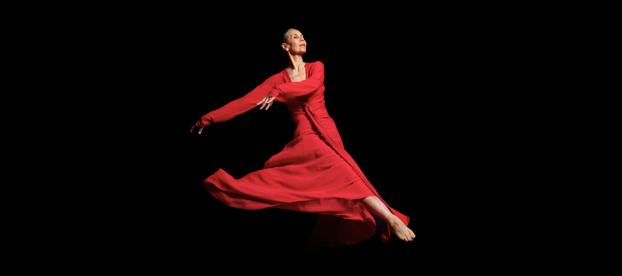 An older woman dances in a flowing red dress, appearing as if she's floating through space. Her face is turned to the right and she wears an expression of calm and fulfillment.
