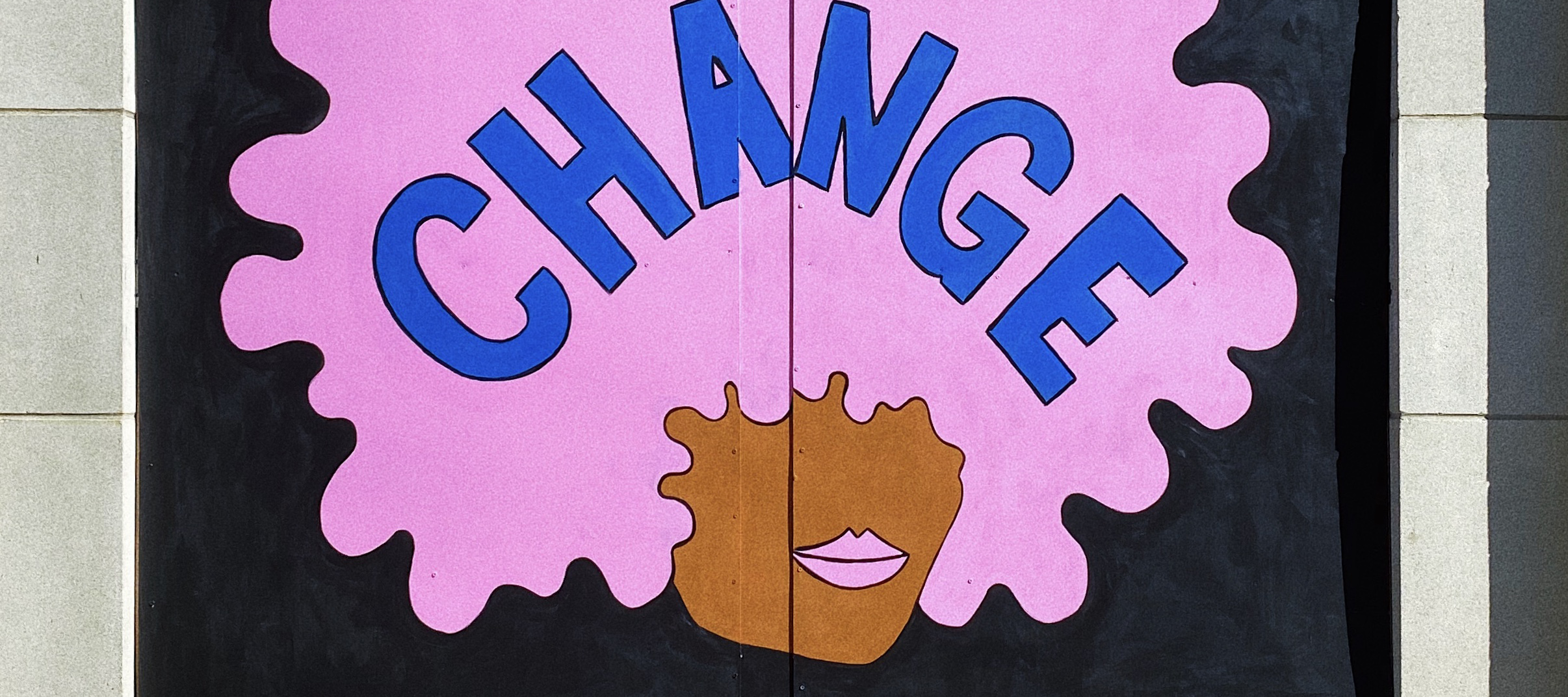 A plywood mural of a dark-skinned face with a bubblegum pink afro and matching, full lips, against a black background.