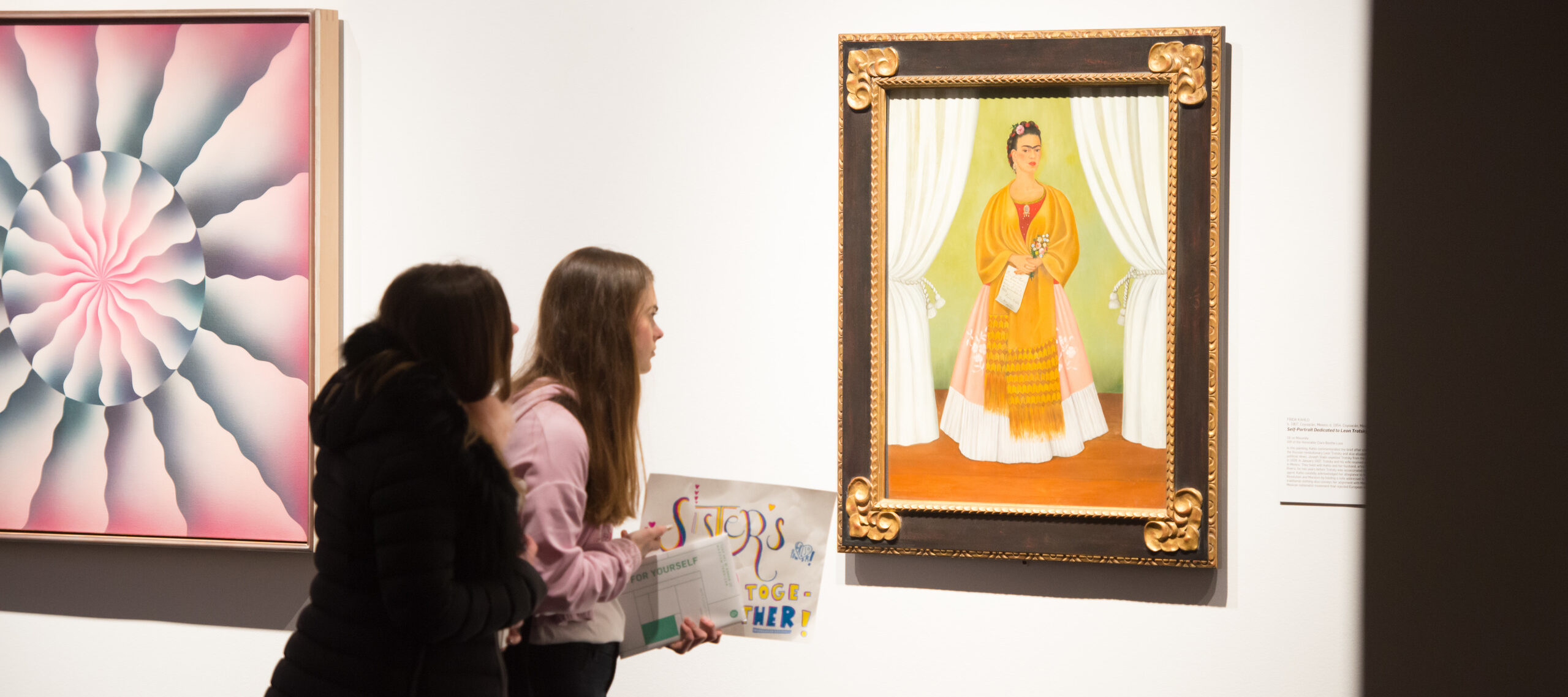 Two young women face away from the camera, craning to get a closer look at a self-portrait by Frida Kahlo