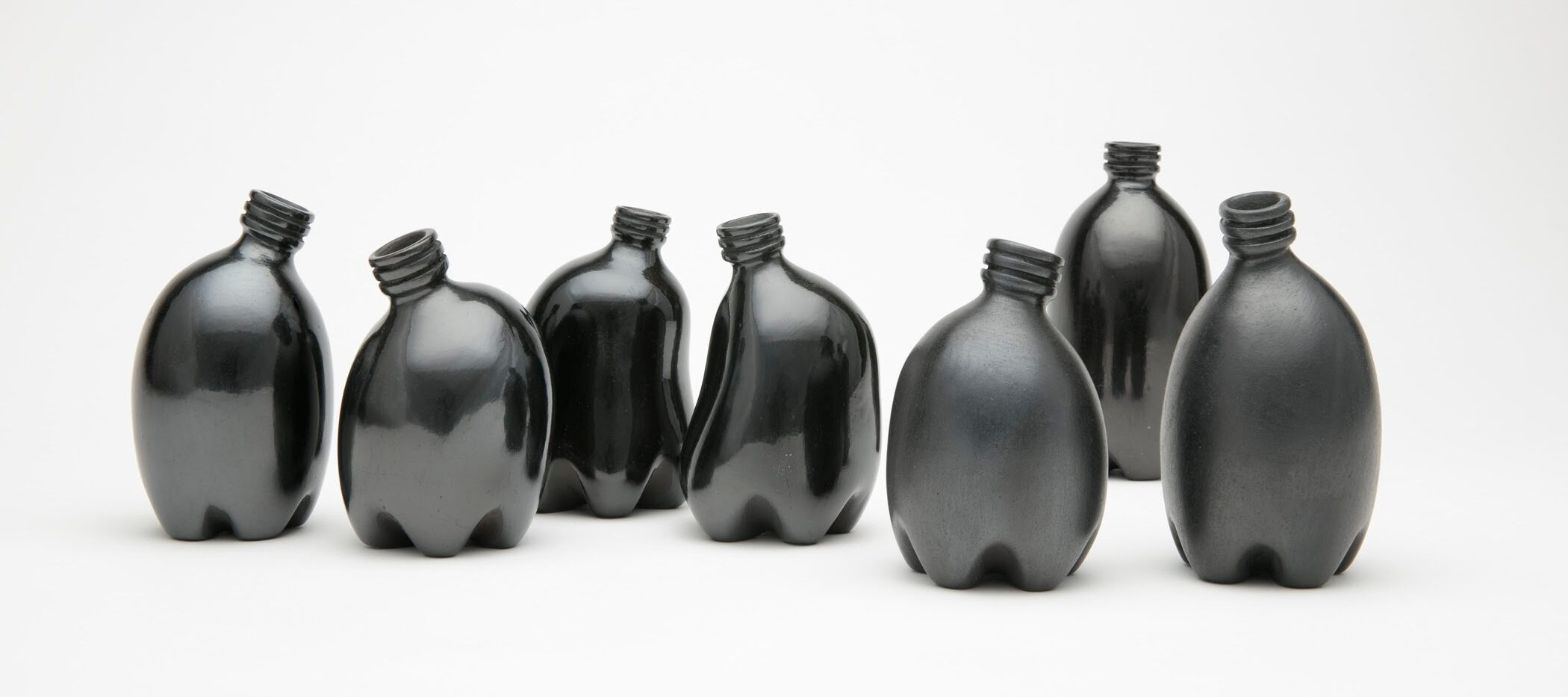 Against a stark white background are seven small clay vessels painted a dark, shiny black. They look like miniature plastic water bottles and are each slightly bent, making them appear like a gathering of people interacting.