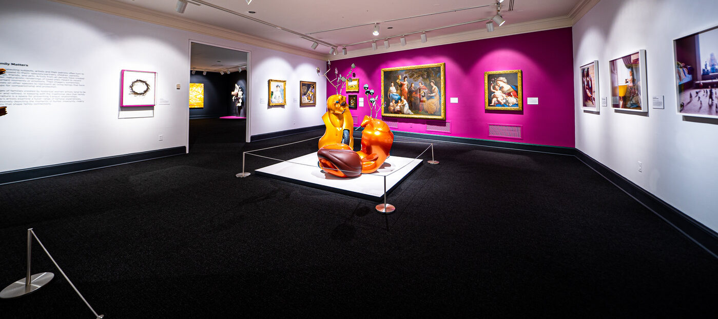 Gallery view with contemporary sculpture made of orange motor scooters that resemble two antlered animals fighting in foreground. Four paintings hang on a magenta wall in background, including a baroque painting of the Virgin and Child, and a portrait of a light-skinned man, women and children gathered together in eighteenth-century attire. To the left on a white wall hang two other paintings.