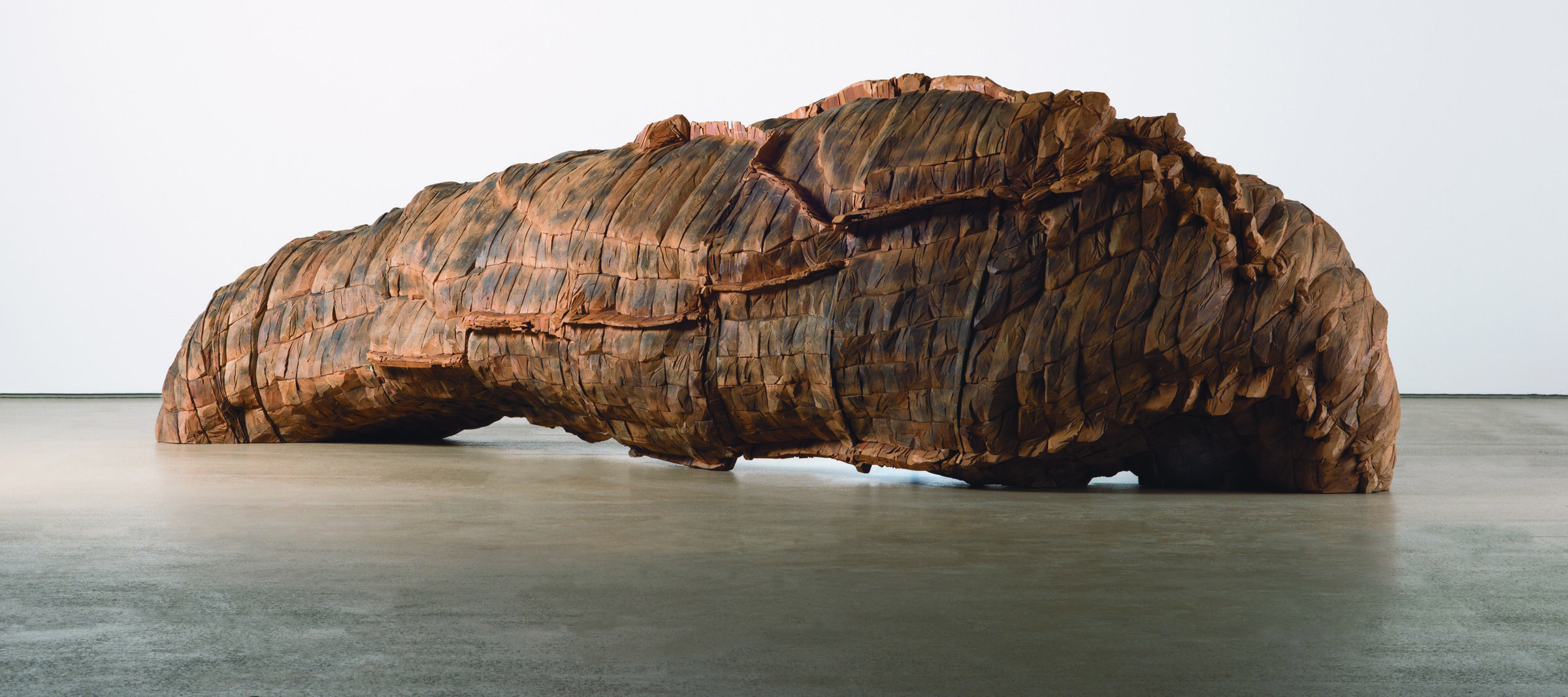 A large cedar and paint sculpture installed against a white wall.