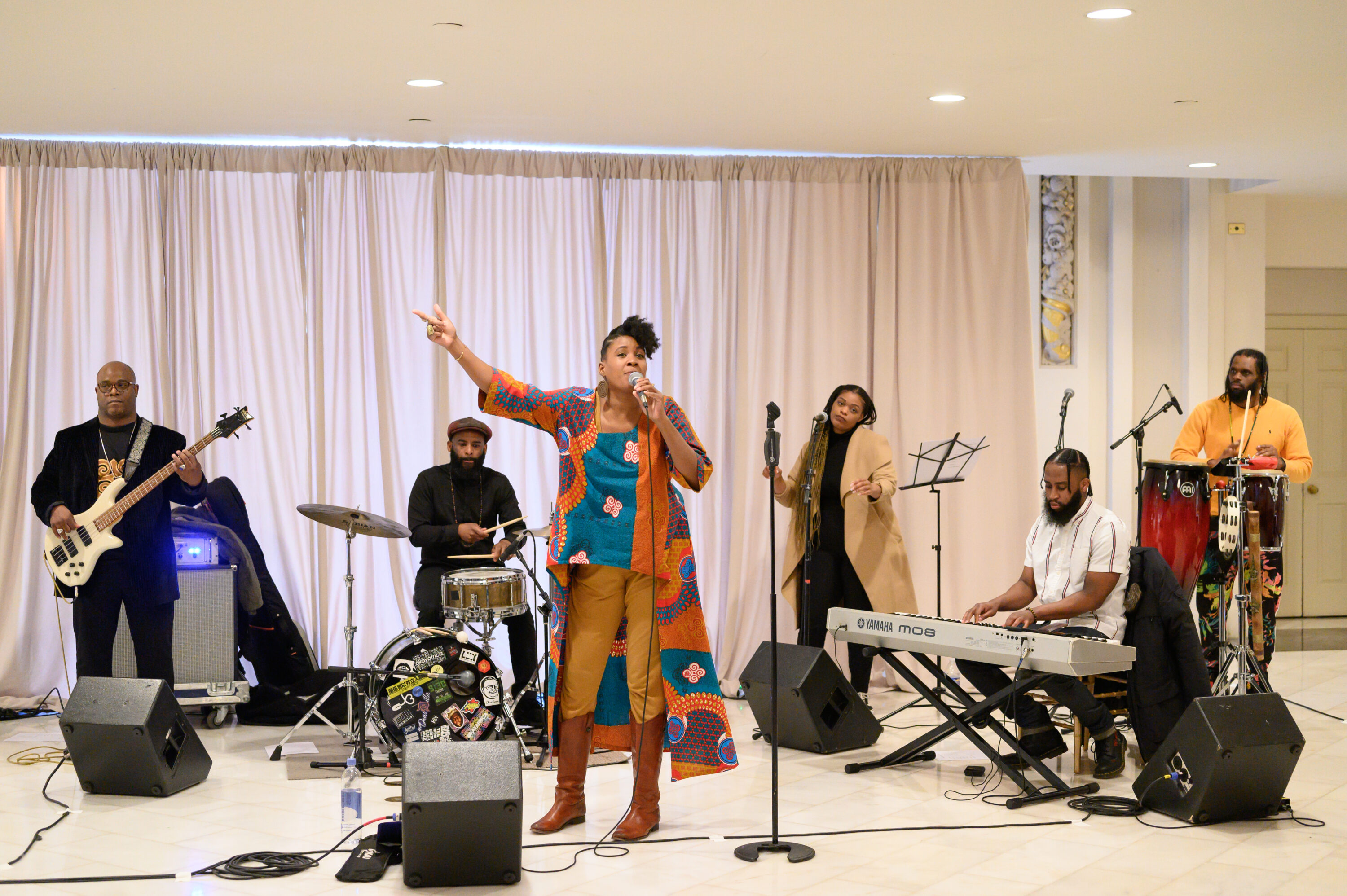 A medium skin-toned adult woman wearing colorful clothing sings into a microphone while a medley of musicians play behind her.