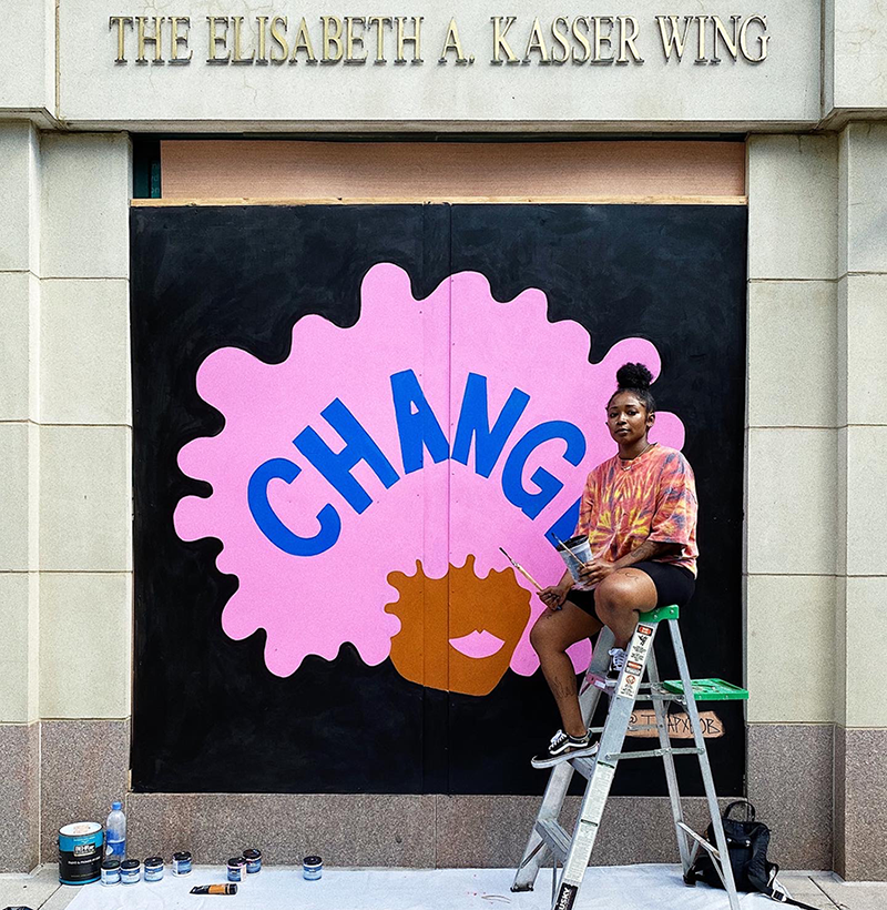 """A dark-skinned woman holding paint and paintbrushes sits on a ladder and looks at the camera. Behind her, a mural depicts a dark-skinned stylized head with bright solid pink Afro and lips. The word """"change"""" is painted in navy capital letters across the expanse of hair."""