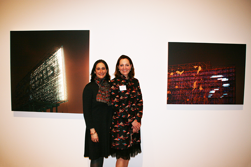 A color photograph of two light-skinned women. They each wear a knee-length dress and have shoulder length brown hair; they stand close together to smile for the camera. Behind them on a white gallery wall are two large photographic prints of the backs of stadium lights.