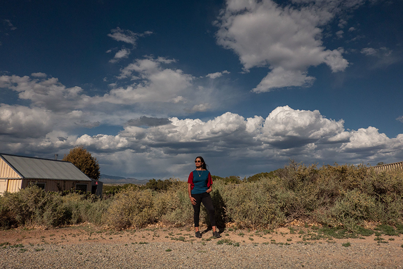 A woman stands on the side of a gravel road. She faces the camera with one hand in her pocket and looks into the distance as the wind blows her long black hair. A house stands in a field of dense shrubbery behind her; a wide blue sky with dramatic cloud stretches above her.