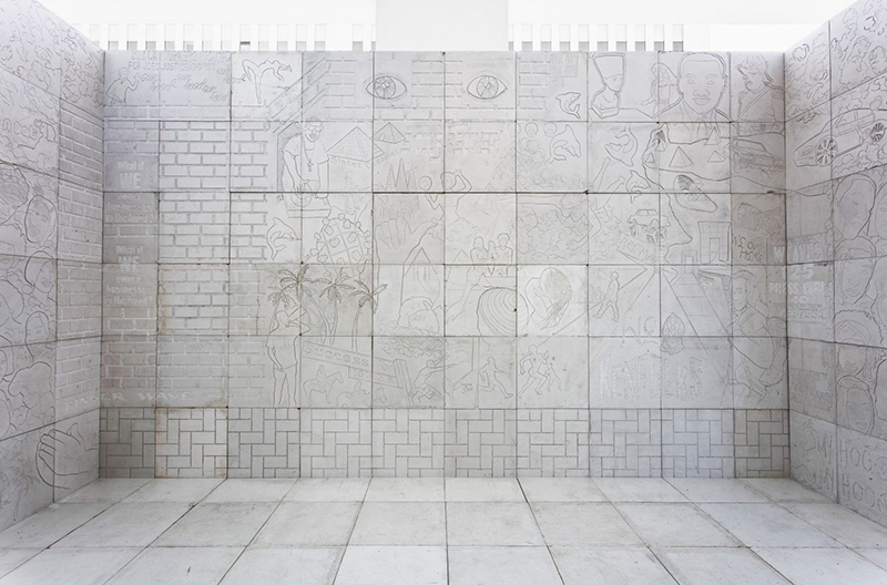 Square blocks of white marble create an open-ceilinged room in the middle of a gallery. The marble walls are inscribed with outlines of overlapping figures, objects, and animals, including Egyptian pyramids, Martin Luther King, Jr. and the bust of Nefertiti.