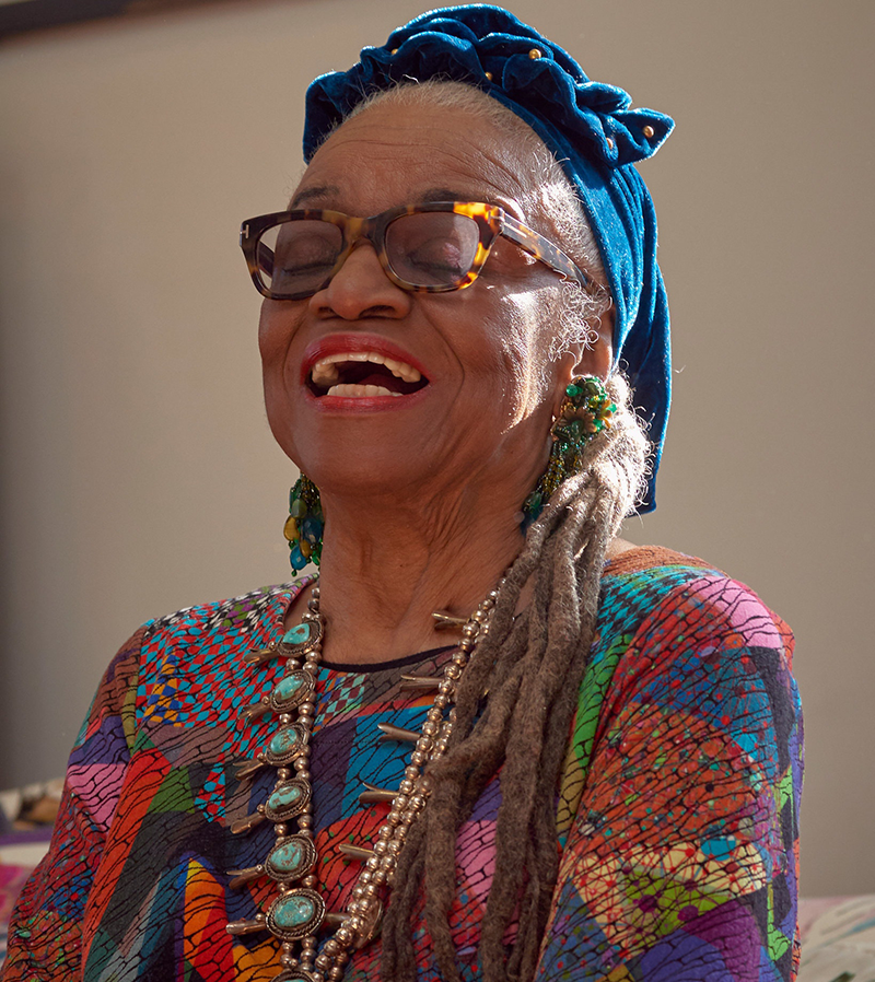 An older dark-skinned woman laughs with her eyes closed and head tilted back. She wears a colorful patterned tunic, a chunky beaded necklace, dangling blue and green earrings, thick glasses, and a blue headscarf that is knotted at the crown of her head.