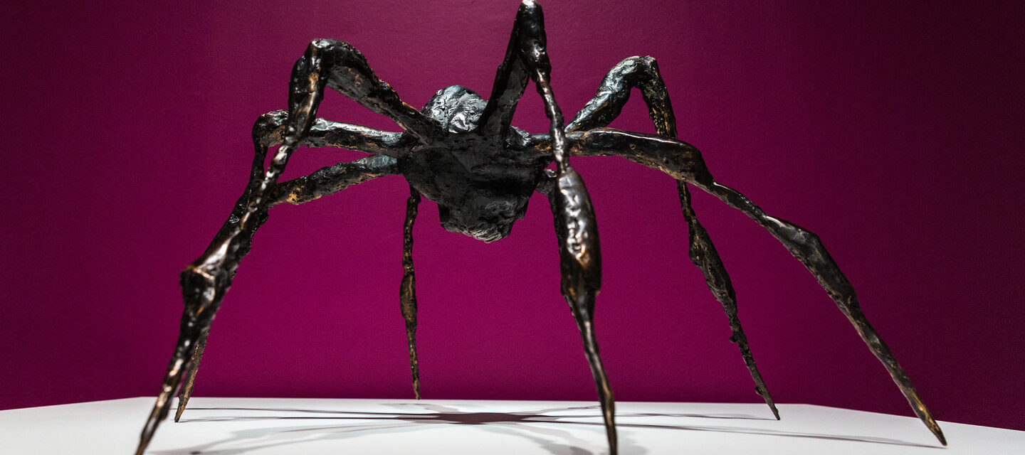 Bronze sculpture of a spider on a white platform against a magenta background.