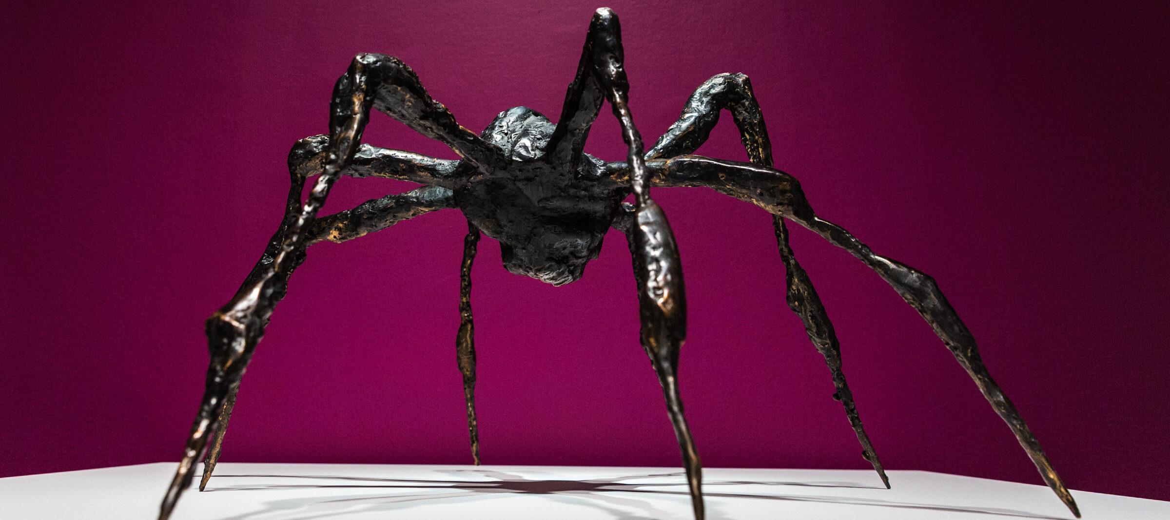 Bronze sculpture of a spider on a white platform against a magenta background.