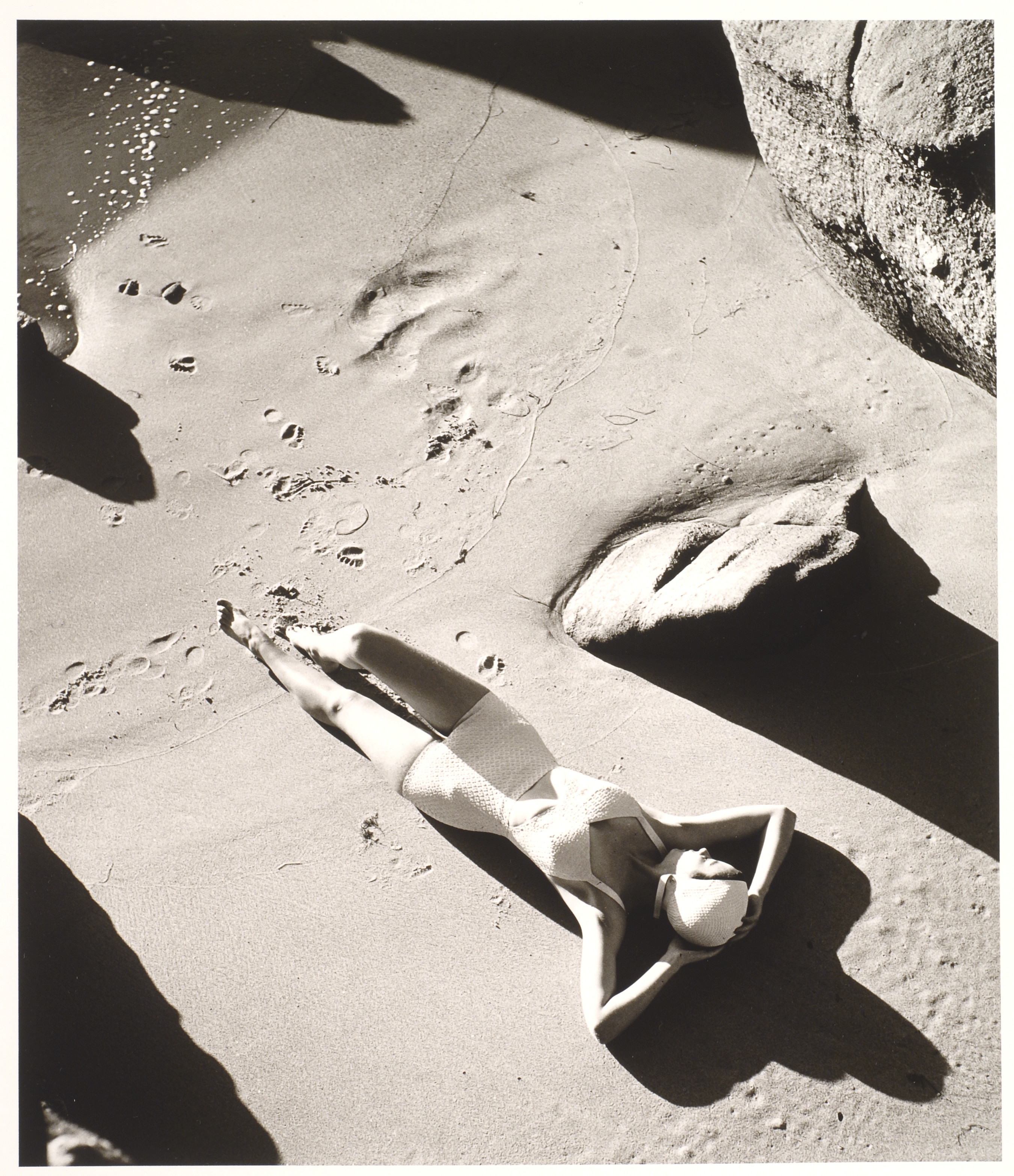 A black and white photograph of a light-skinned woman wearing a one-piece white bathing suit and white swim cap. She is lying down on sand with her hands behind her head. There are footprints in the sand below her, and the image is framed by large rocks.