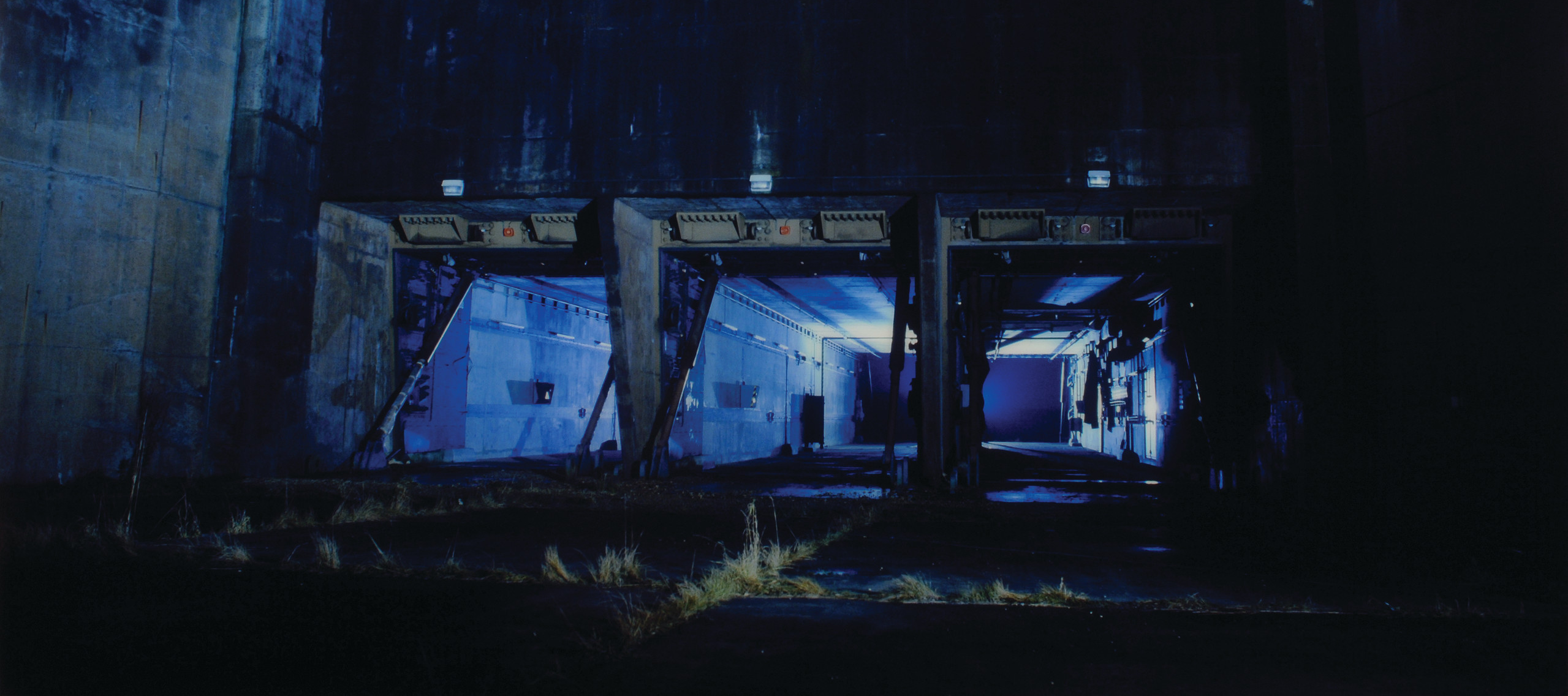 Eery photograph in blue tones of a concrete silo at night.
