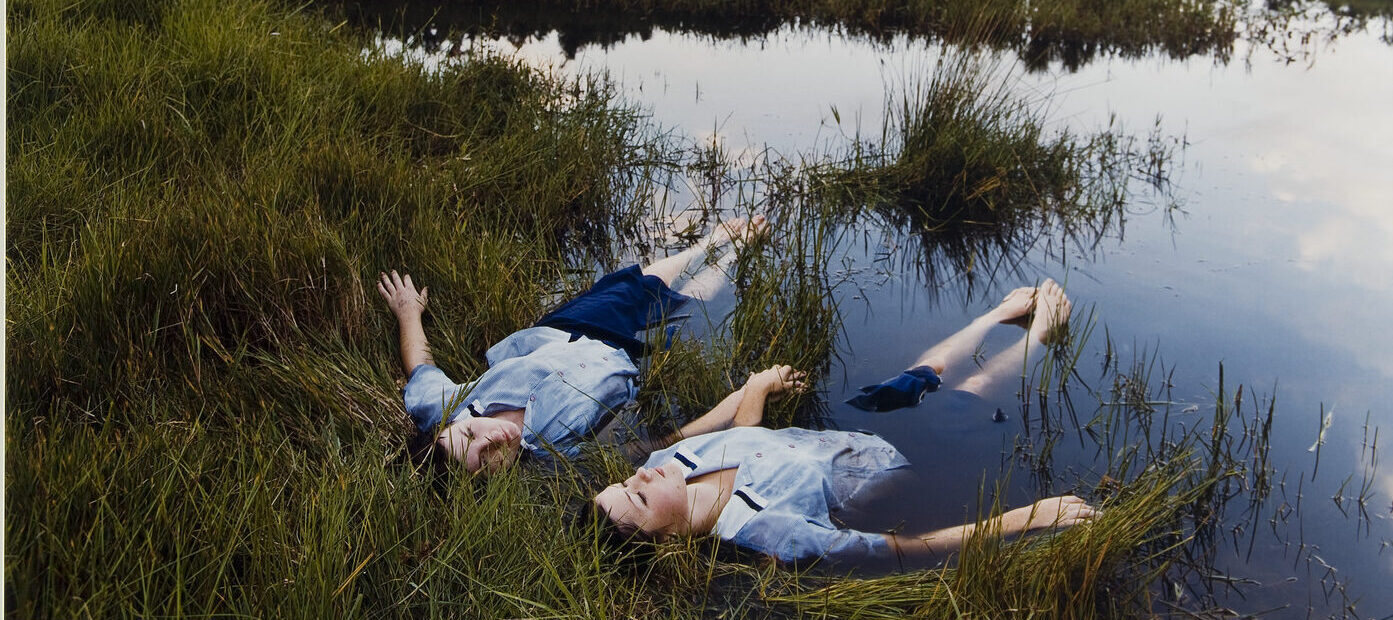 Two adolescent girls with light skin wearing matching blue uniforms float side-by-side on the edge of a grassy pond while holding hands.