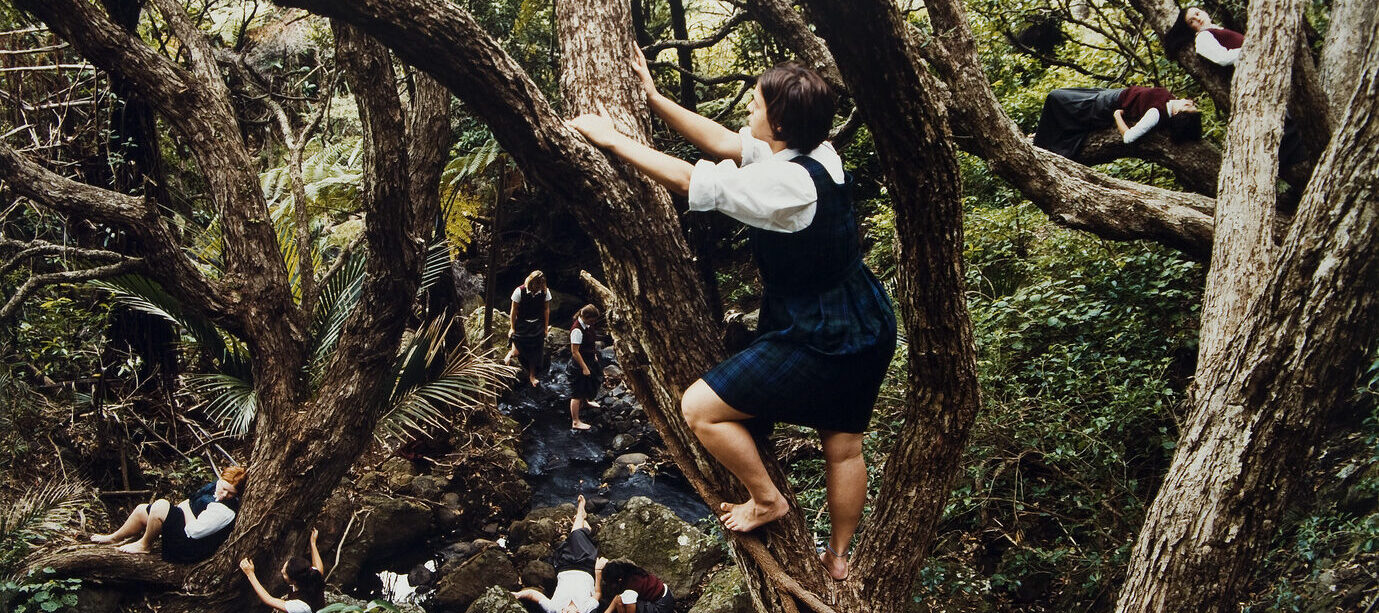 Color photograph of a dense forest with a light skin-toned girl with bare feet climing a tree at center. Below her to the right is another light skinned girl sitting against the trunk of a tree. Other figures are scattered throughout the forest in the background.