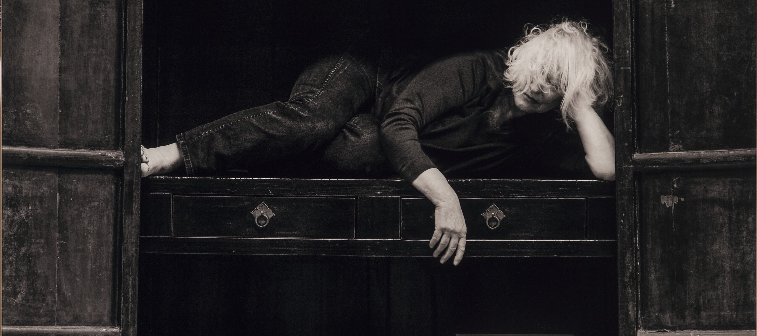 A black-and-white self-portrait of a light-skinned older woman with shoulder-length blonde hair who lays on the middle shelf of a large wooden cabinent. She is in a relaxed fetal position; one hand props her head up and the other is draped over the shelf. Above her a collection of tiny statues are arranged by size, on the shelf below her are a tea pot and two boxes.