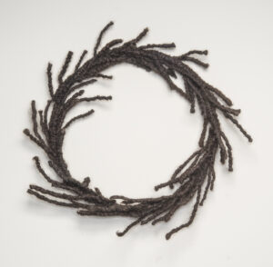 A circular wreath made of tightly coiled hair with strands escaping.