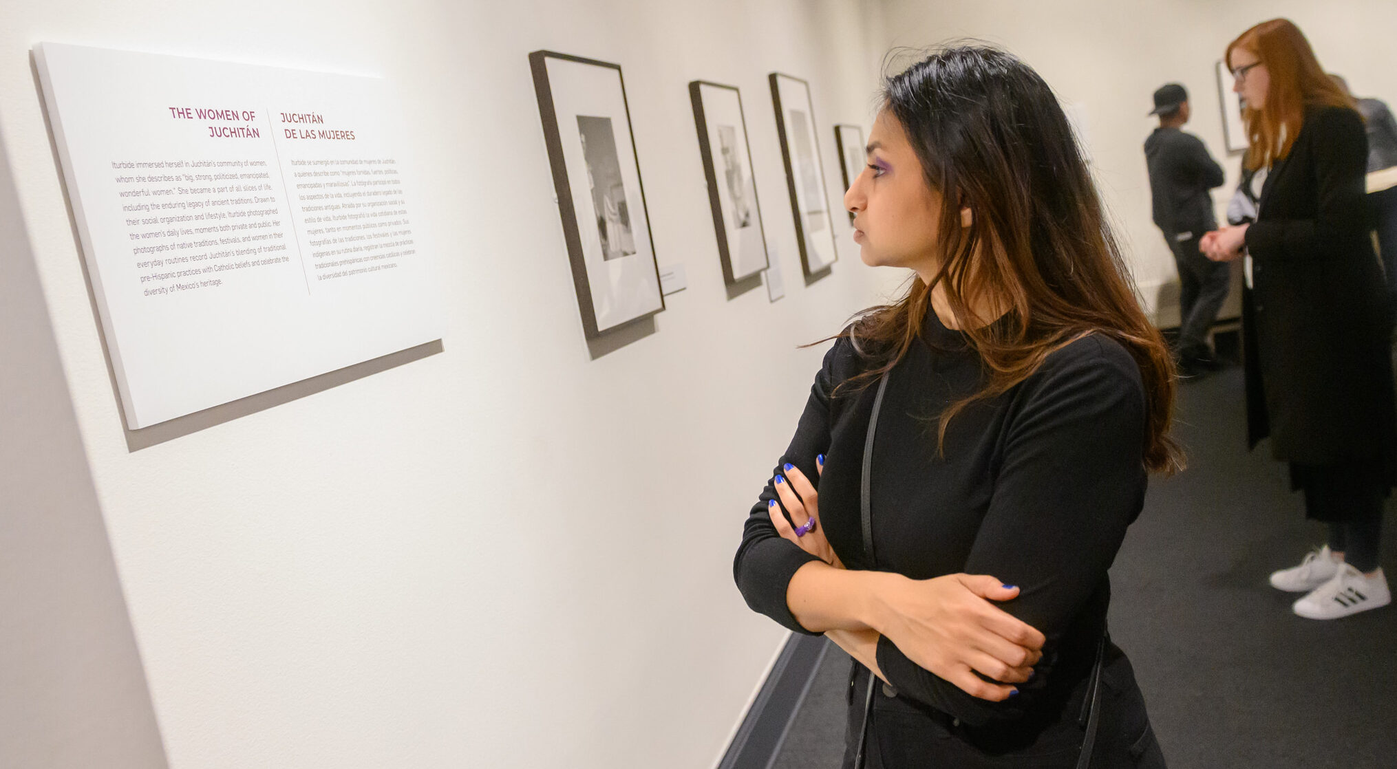A medium light-skinned young woman in a black top crosses her arms while reading a gallery exhibition label intently.