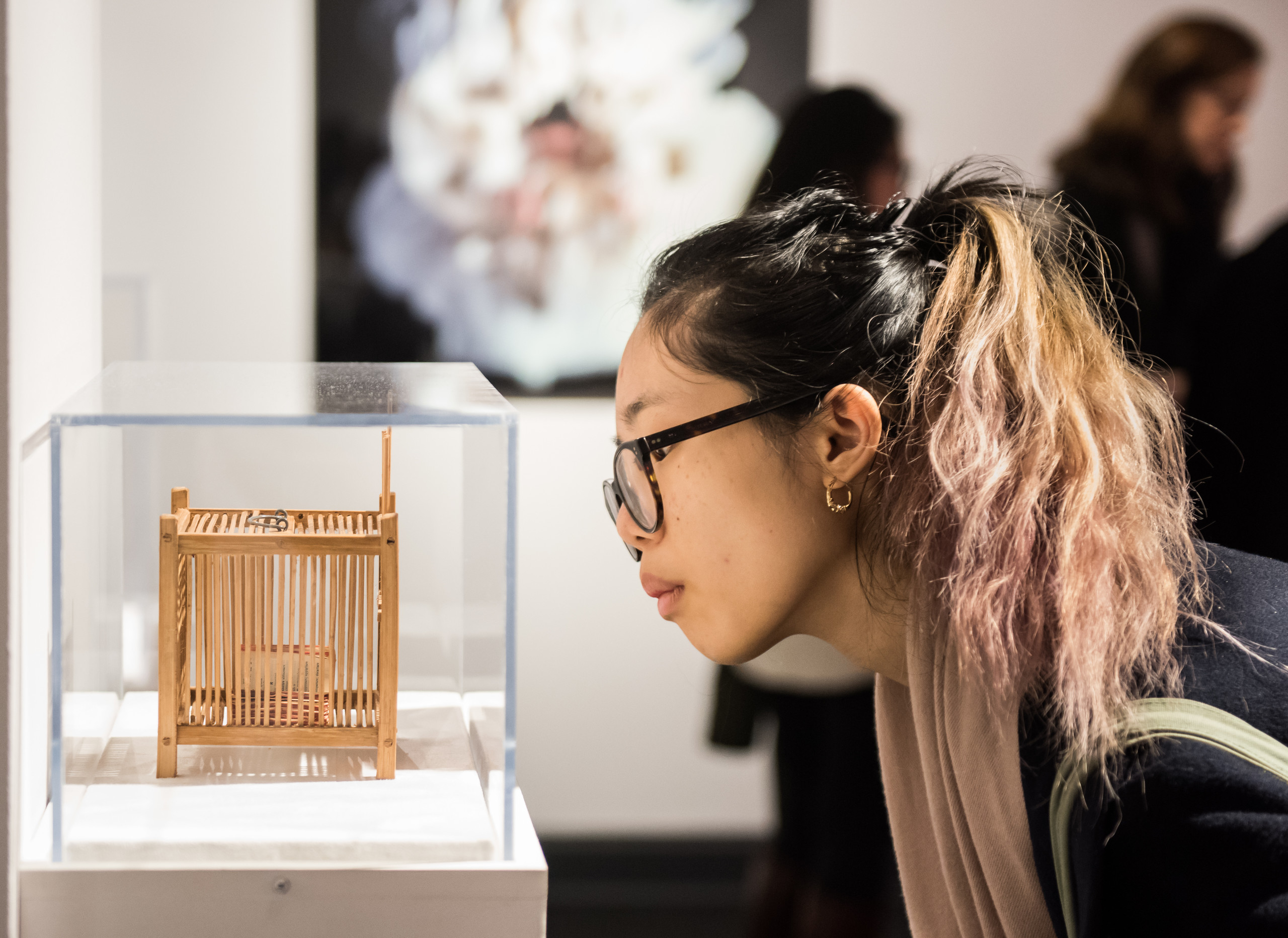 Partial gallery view of a young woman in a ponytail and glasses bending down to look at a tiny contemporary sculpture in a glass vitrine. The sculpture is a wooden cage with an object stored inside. On the back wall hangs a photograph of a light-skinned woman in a white dress.