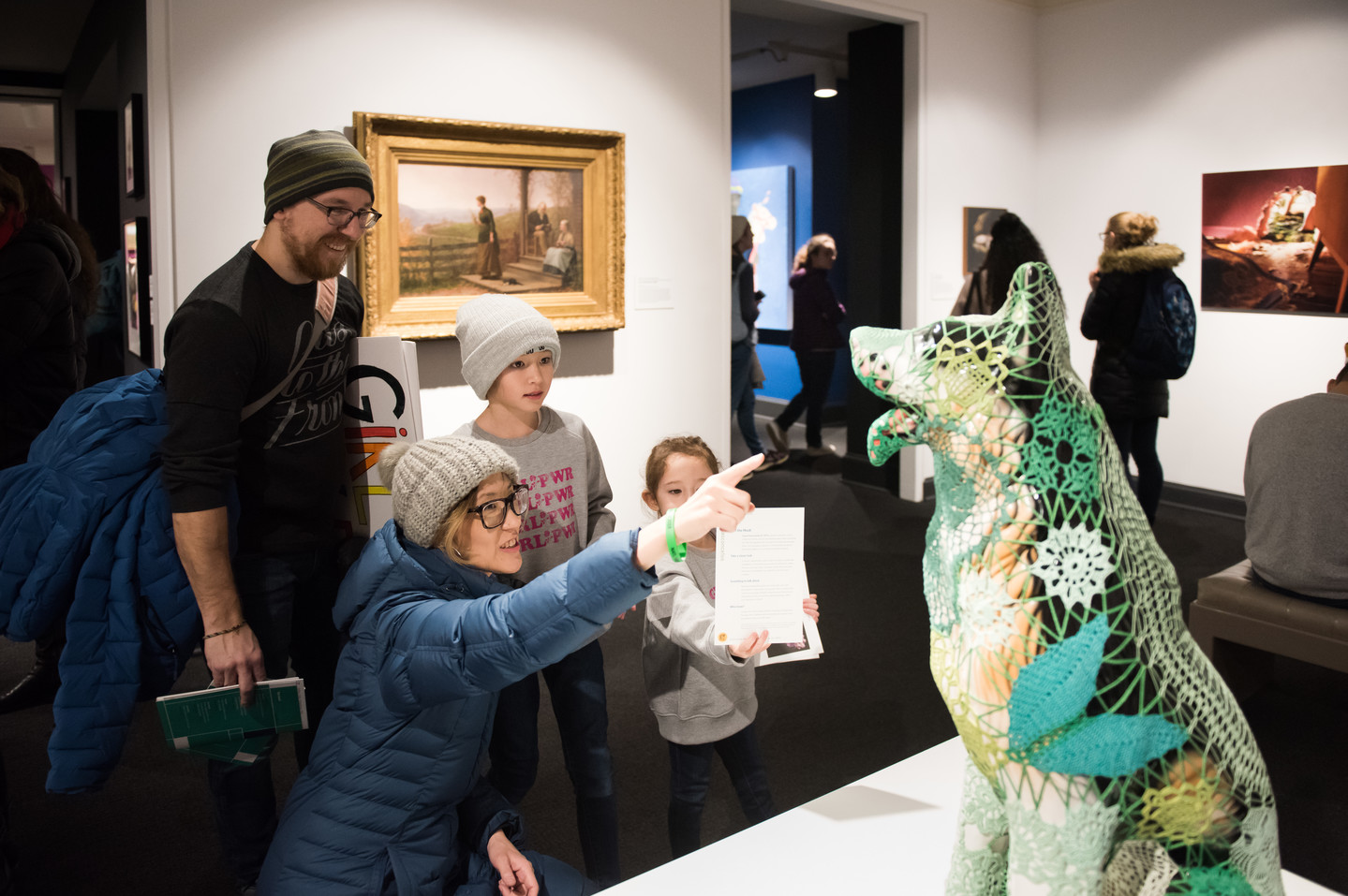 Gallery view of visitors looking at a contemporary sculpture of a dog covered in green knitting in the foreground. A woman kneels pointing at the dog, while a man and two children stand next to her. A gilded framed painting of a woman standing on her porch and looking out into a field hangs on a wall behind the central group and other visitors look at artwork in the distance.