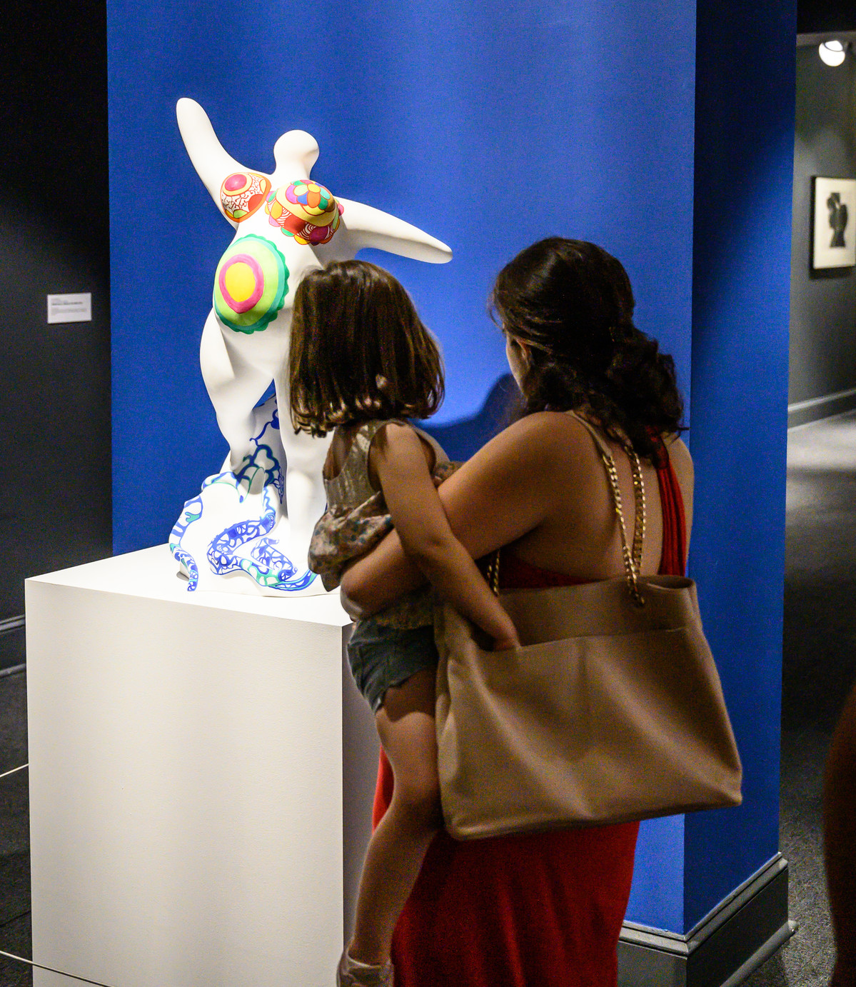 Partial view of a gallery with a woman carrying a child in her arms. Both figures with their backs facing the camera look at a contemporary marble sculpture against a deep blue wall. The faceless sculpture has a voluptuous white marble body, arms outstretched, and brightly-painted designs on its breasts and stomach.