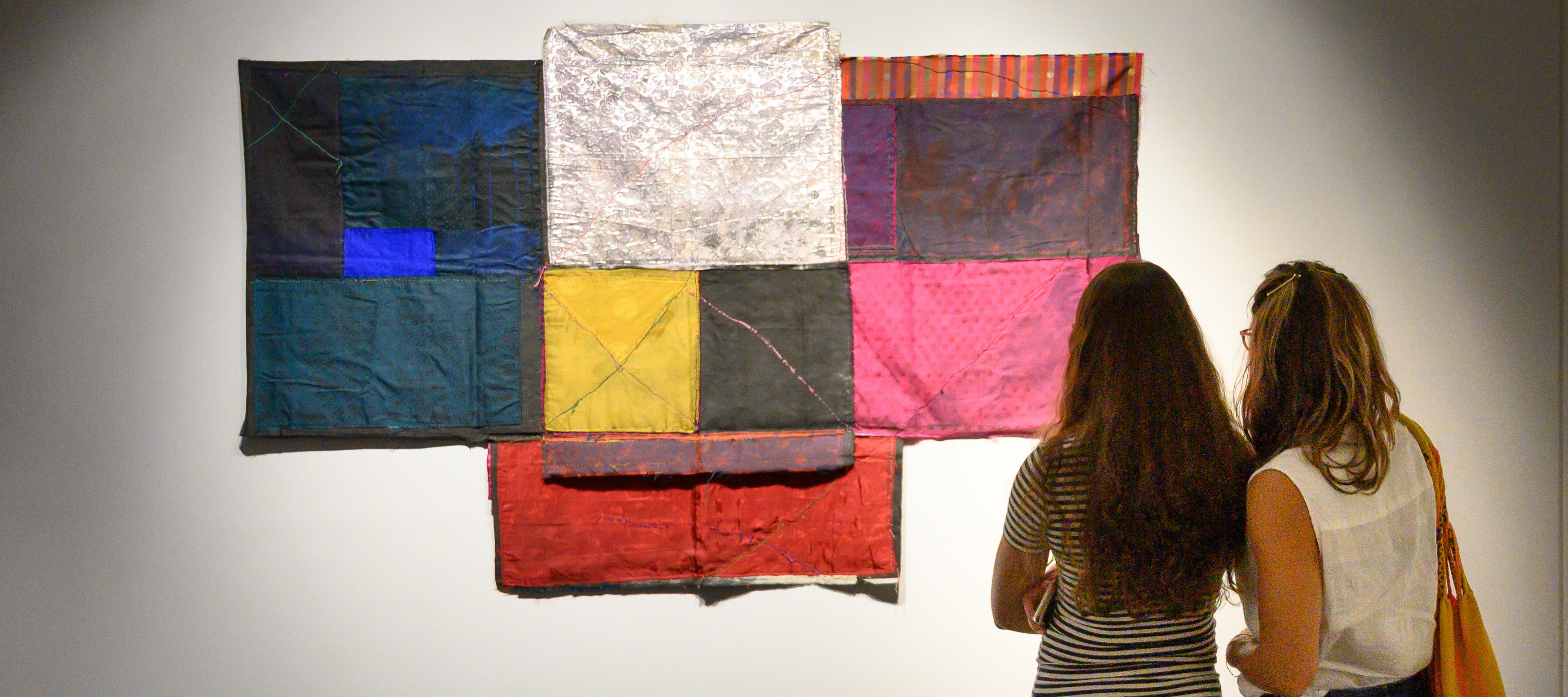 Two people standing next to each other in casual clothes with long hair seen from behind; they are looking at a t-shaped, colorful textile collage artwork hung on a white gallery wall.