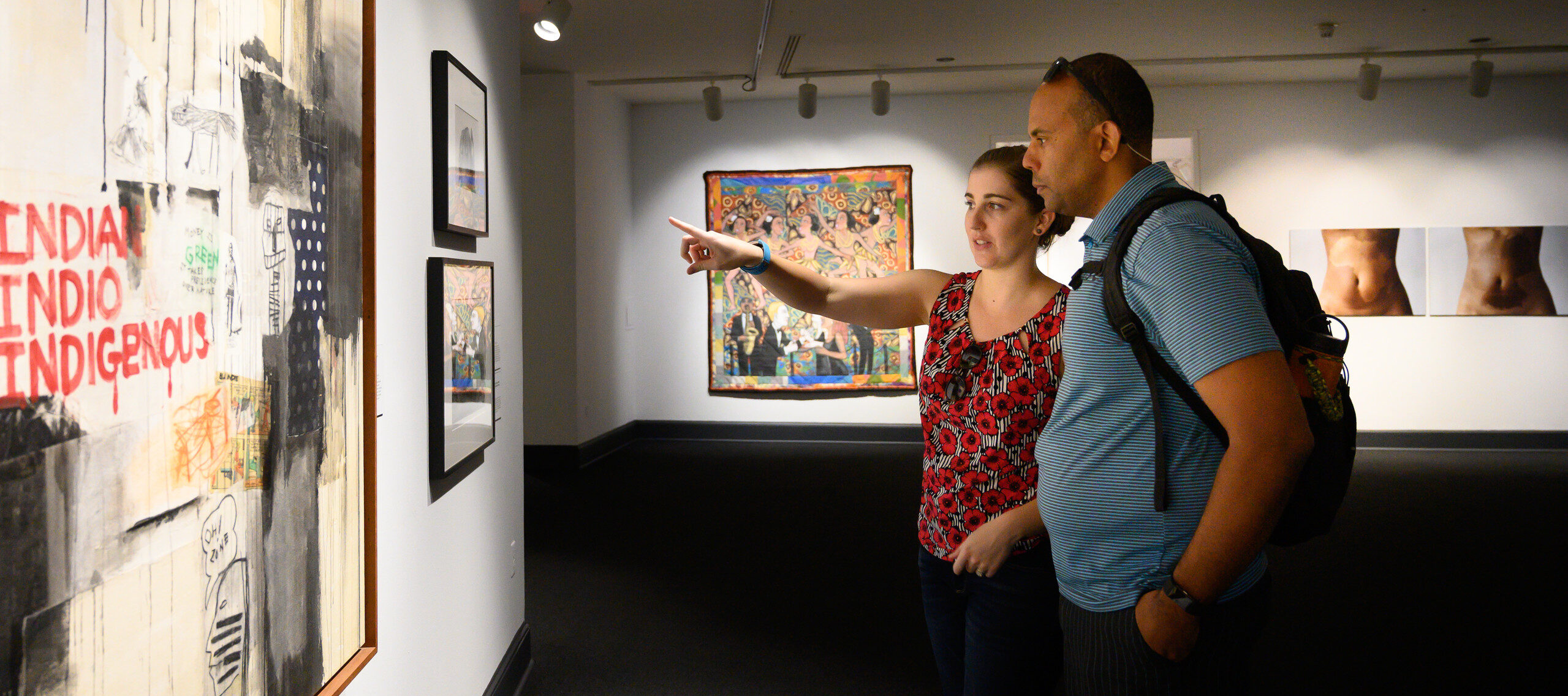 "Partial gallery view of a man and woman pointing at framed artworks on a wall. The large work in the foreground has the words ""INDIAN INDIO INDIGENOUS"" in red hand-drawn letters against a background of red and black painted sections and drips."