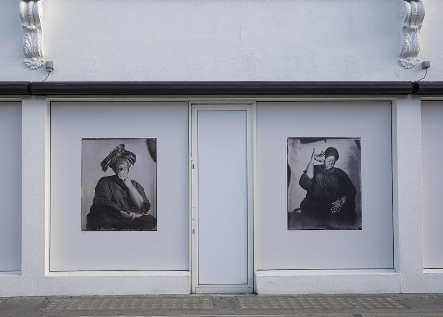 Two poster-size black and white photographs, each an artful portrait of a dark-skinned woman with her hand to her face in one, and holding a shell to her ear in the other, occupy the façade of a low white city building.