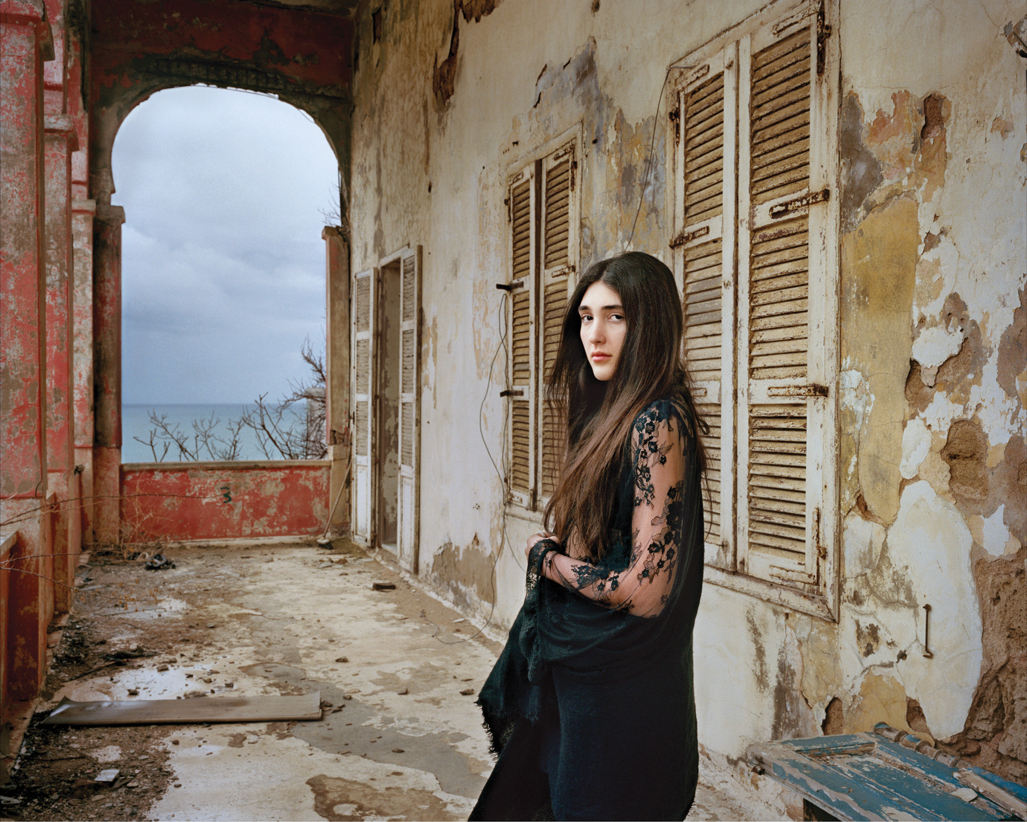 A light-skinned young woman with long, dark brown hair in a black, long lace sleeved dress stands confidently in a crumbling loggia. She gazes at the viewer with a serious, captivating look.