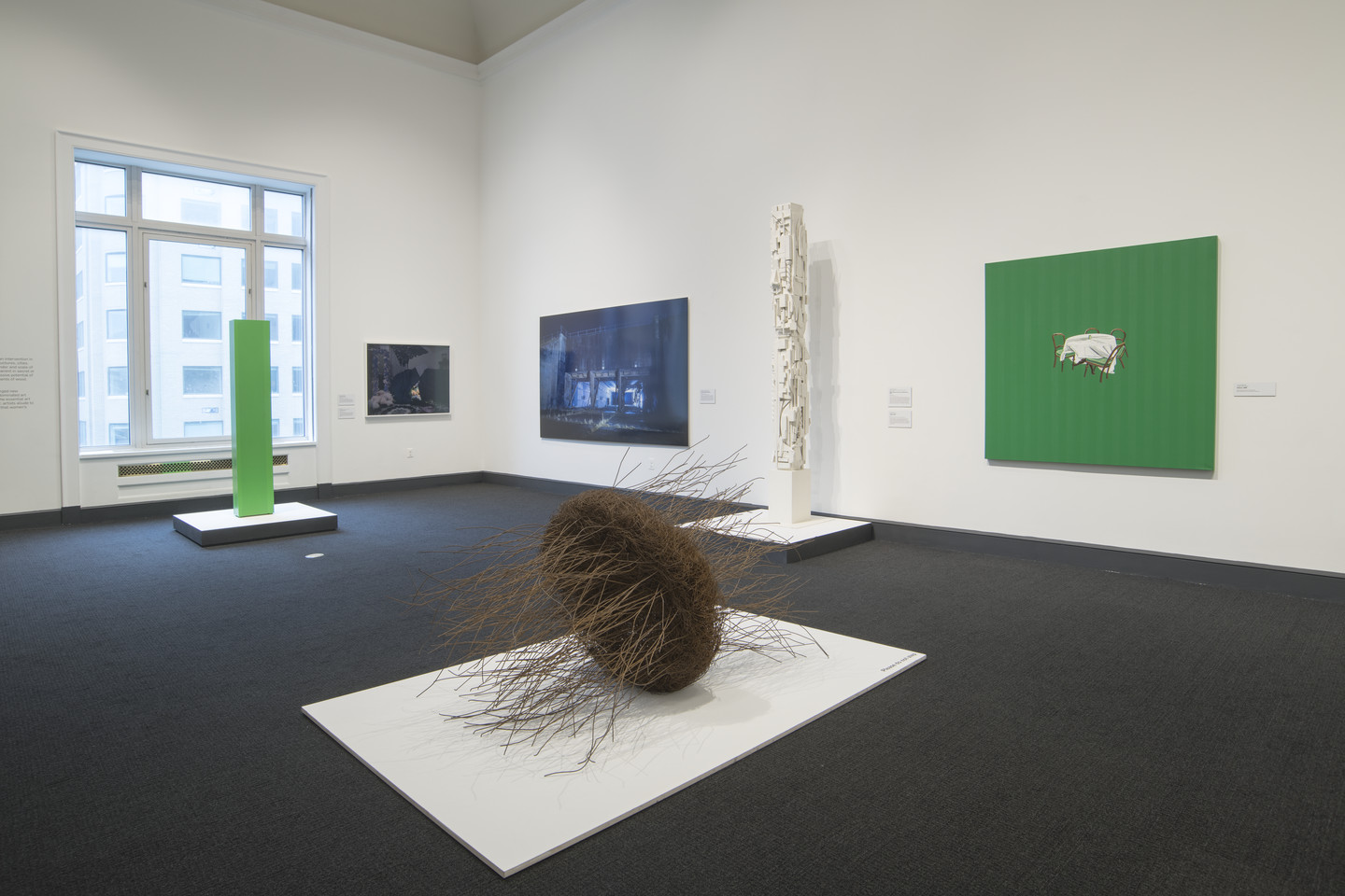 Partial view of a gallery with six contemporary artworks, including painting of small chairs and table with white tablecloth centered on a neon green background, two photographs on adjacent walls, three sculptures rest on white platforms on the floor.