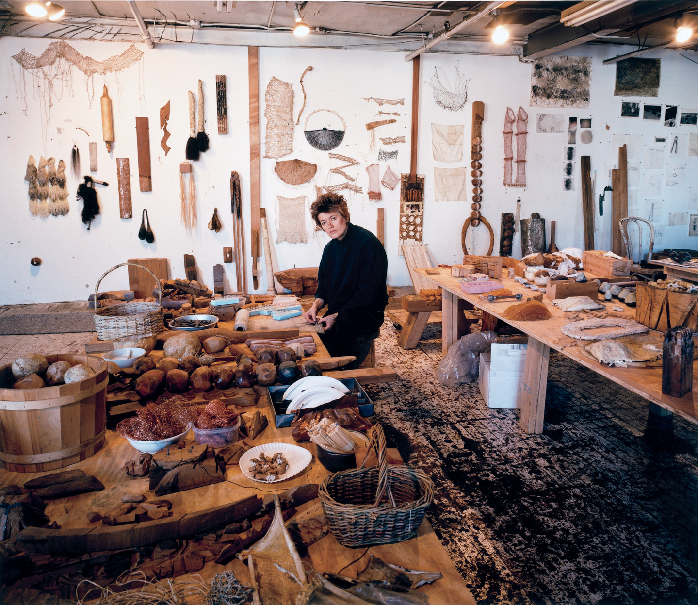 A light-skinned woman with close-cropped hair stands between two large plywood tables, looking up from her work. The tables and walls are filled with natural objects and artworks, including hanging weavings, spools of thread, carved wooden rocks, and wicker baskets.