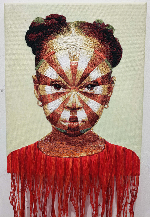 An embroidered portrait on canvas of a young medium-dark skinned girl from the shoulders up. She looks directly at the viewer; her face has the pattern of a dart board on it. Her shirt is made from bright red thread, which hangs off the bottom of the canvas loosely.
