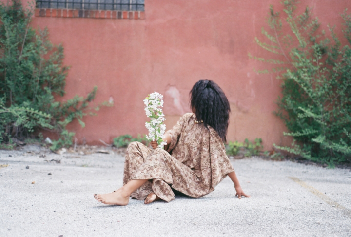 A dark-skinned woman in a flowing brown patterned tunic sits barefoot on a cement ground, leaning back on her left hand. In her right hand, she holds a stalk of white flowers; her head is turned away from the camera and faces a pink clay wall behind her.