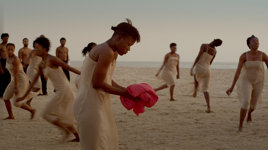 A group of dark-skinned women wearing tan-colored slip dresses run gracefully on an empty beach at twilight. One woman in the center stands still, her shoulders hunched over a pink bolt of cloth in her hands. Behind them, dark-skinned men stand without shirts stand and watch. The colors are muted and dream-like.