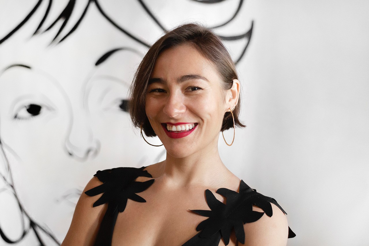 A medium-skinned woman with ear-length straight brown hair smiles widely for the camera. The photograph is cropped from her chest up; she wears a black sleeveless top, red lipstick and gold hoop earrings. Behind her on a white wall the outline of a face, drawn in black outline.