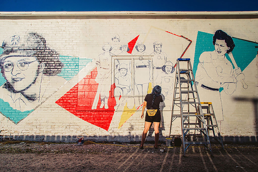 A woman with a yellow fanny pack paints a mural on a white wall in an alley. The mural is unfinished, but shows a group of women in uniforms standing together against a graphic red triangle. Two larger portraits of these women are painted on either side in blue triangles; one is holding a baseball bat. Two ladders stand against the wall.