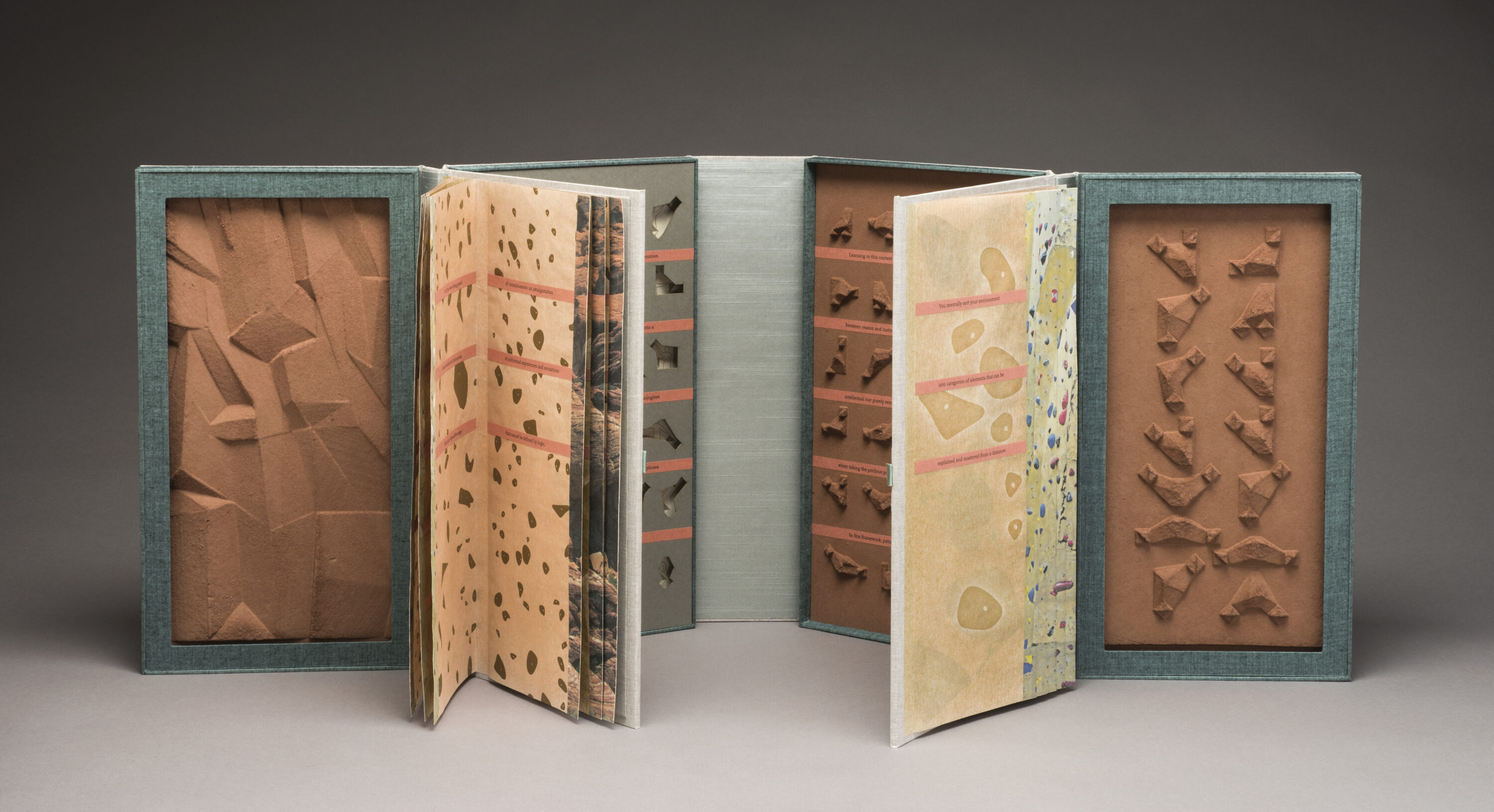 An open artist's book resembling two open books connected end to end. The four inner cover panels feature small sculpted brown shapes, small indented shapes, and a rocky-looking panel. The two groups of pages feature different patterns that resemble rock climbing walls.