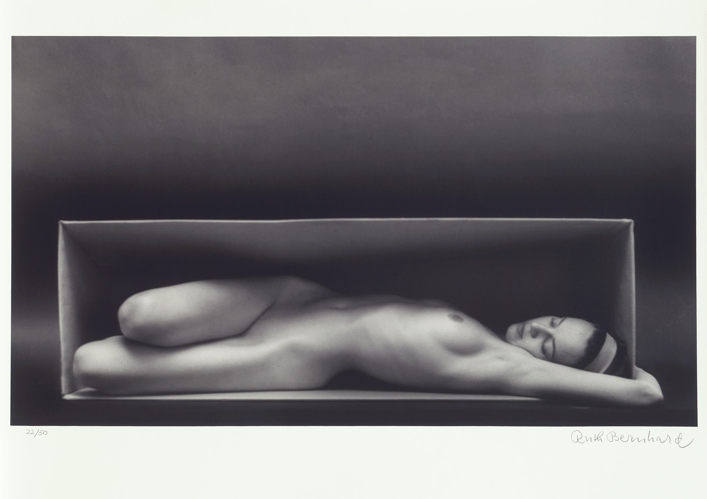 A black-and-white photo of a nude light-skinned woman laying inside the horizontal opening of a box . Her legs are bent at the knees and facing right while the rest of her body is reclined, her left breast exposed to the camera and left extended arm overhead, wrapped around the side of the box. She looks relaxed, with closed eyes and wears a headband.