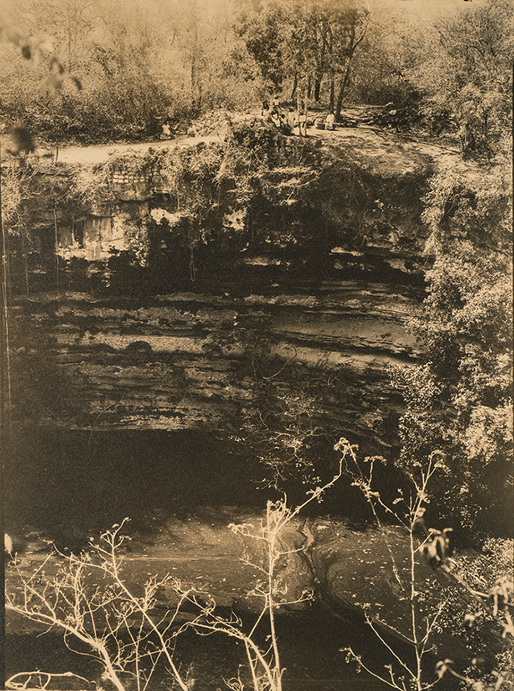 An old sepia-toned photograph of a large swimming hole overgrown with plant life. The massive structure fills most of the frame, with layers of rock visible on the sidewalls; at the top of the composition is an almost indistinguishable group of people visiting the site.