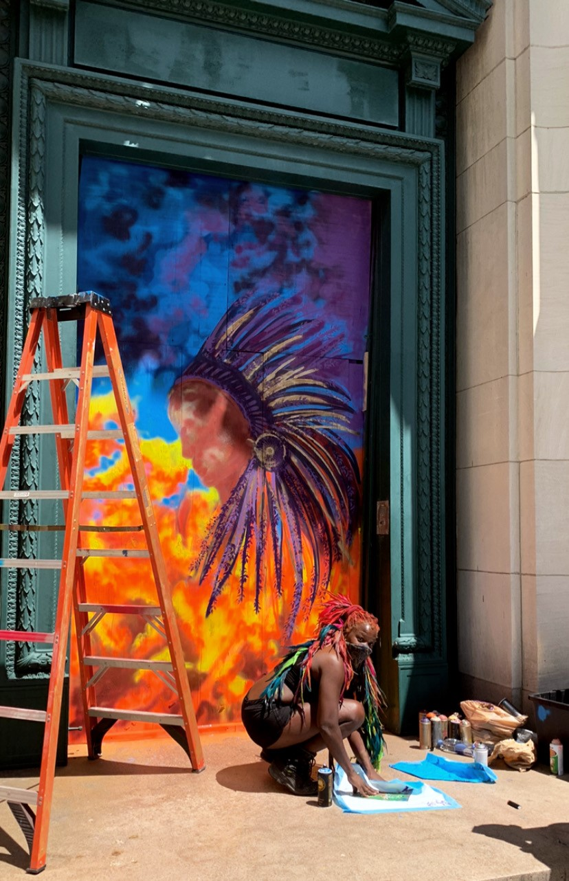 A dark-skinned woman gathers materials on the ground in front of a doorway. She has long bright orange and red hair accentuated with blue and green feathers. In the doorway is a vibrant mural with the profile of a dark-skinned person wearing a sweeping feathered headdress.
