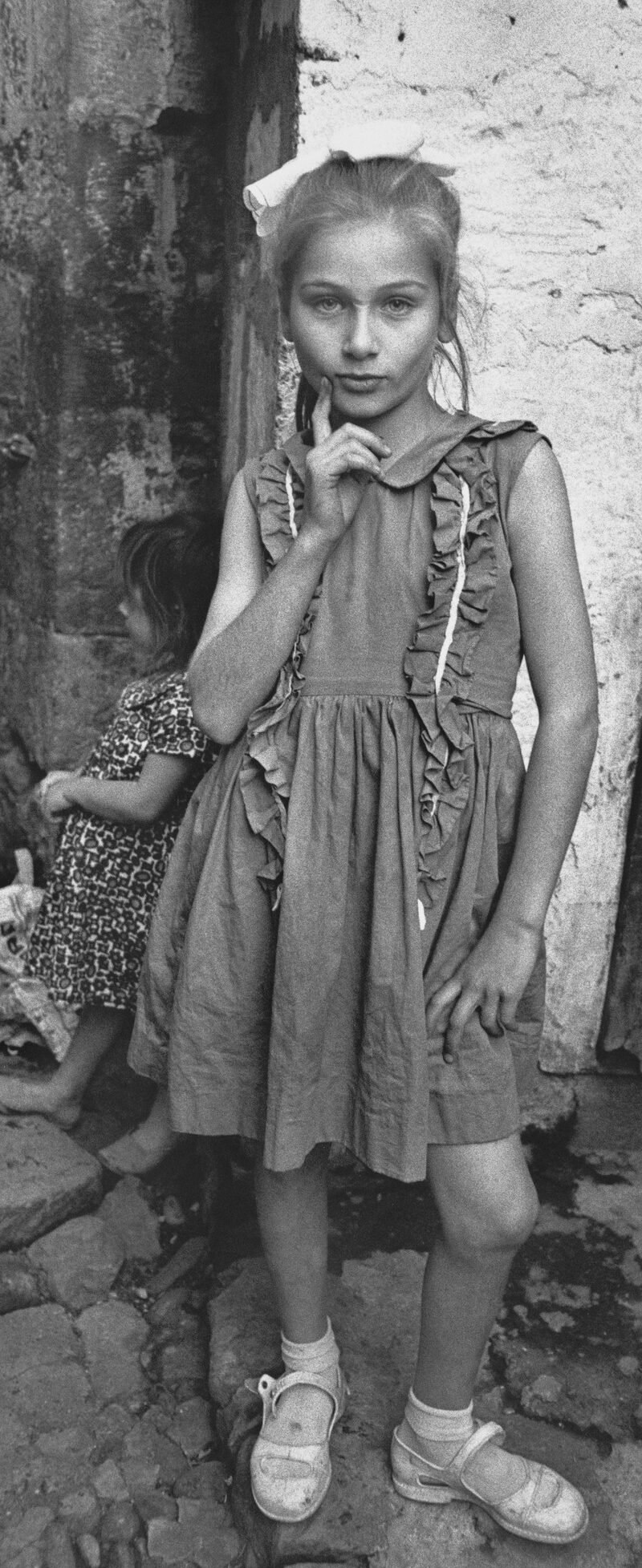 A black and white photograph of a young girl posing with her hip out and hand on her chin. She stares directly into the camera while wearing a ruffled dress, hair bow, and buckled shoes. Behind her is a stone wall that a younger child leans against.