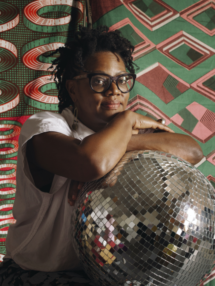 An African American woman sits in front of a green and red lively-patterned background; she stares slightly smiling at the camera, her arms resting on the top of a large silver disco ball and just below her chin. She wears large cat-eye glasses and a white shirt.
