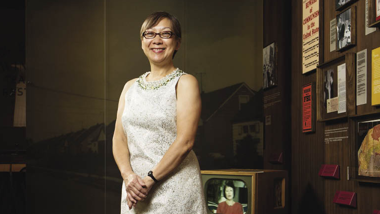 A light-skinned Asian woman stands smiling in front of a historical exhibition showcasing posters and a TV from the 1950s.