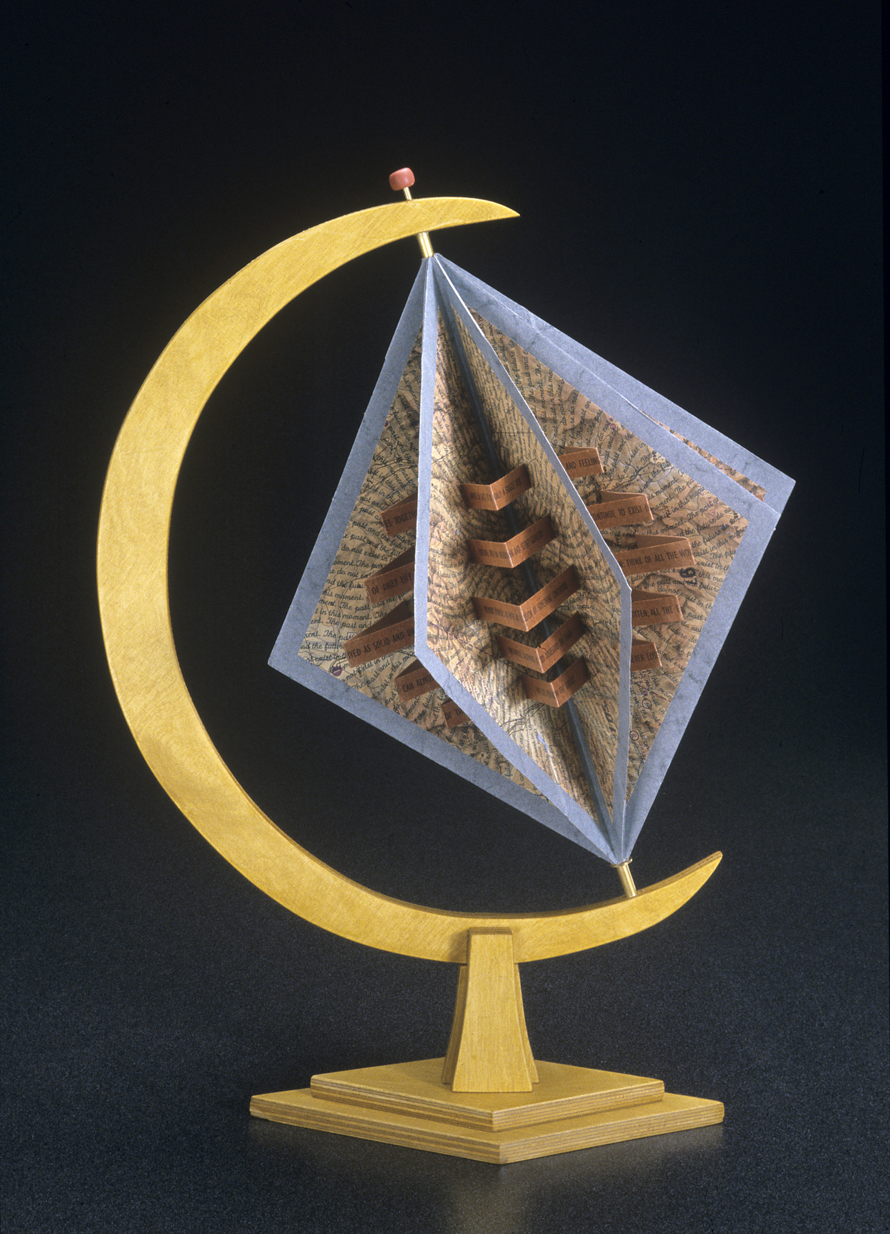 An open artist's book that is diamond shaped with open carousel-style pages covered in lines of text radiating out from the core. The book is perched in a half-moon holder on a stand, like a globe.