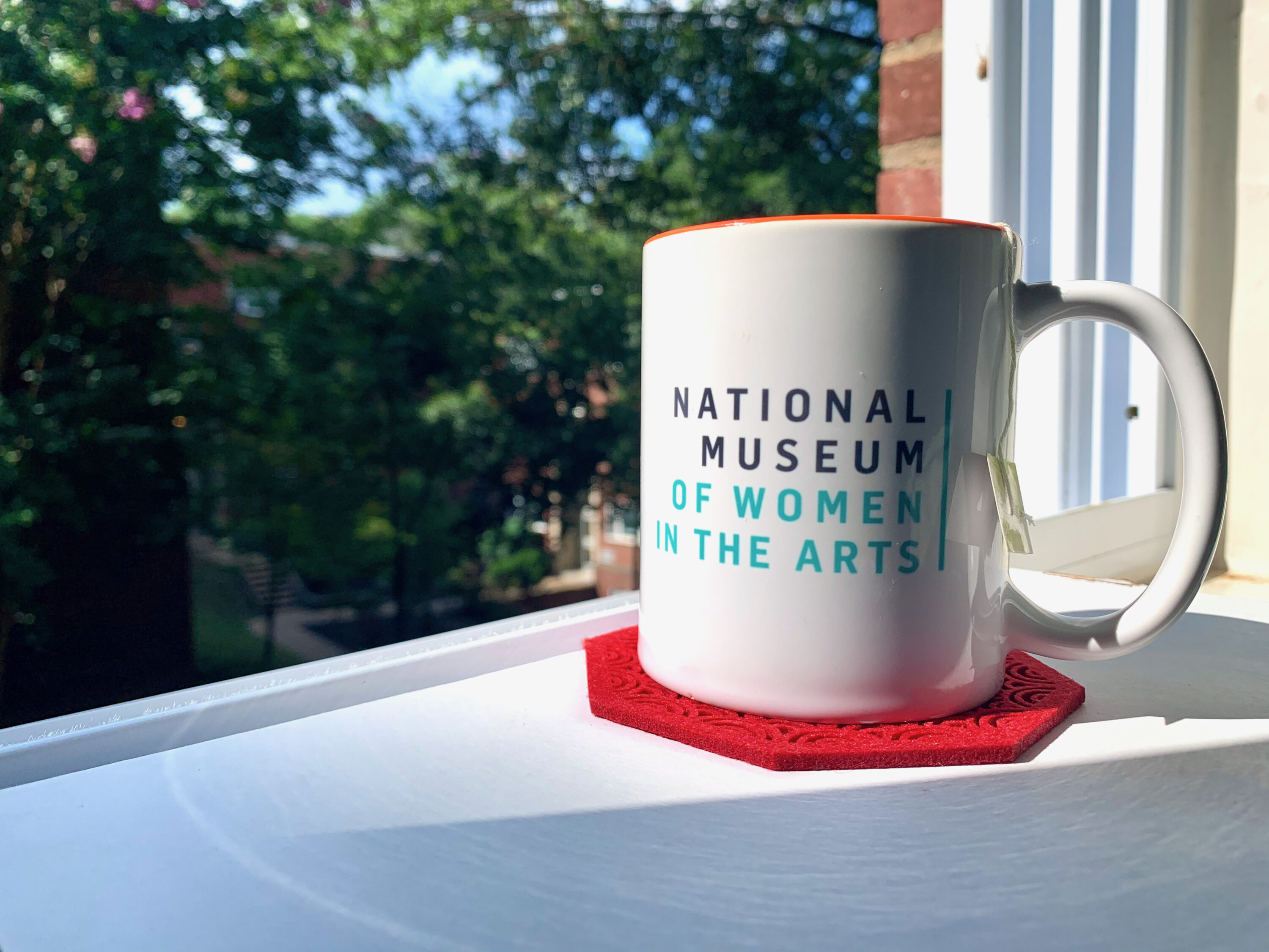 A white mug with National Museum of Women in the Arts printed on it in gray and green text, sitting on a red coaster on a white surface. Behind the mug is an open window showcasing green foliage.
