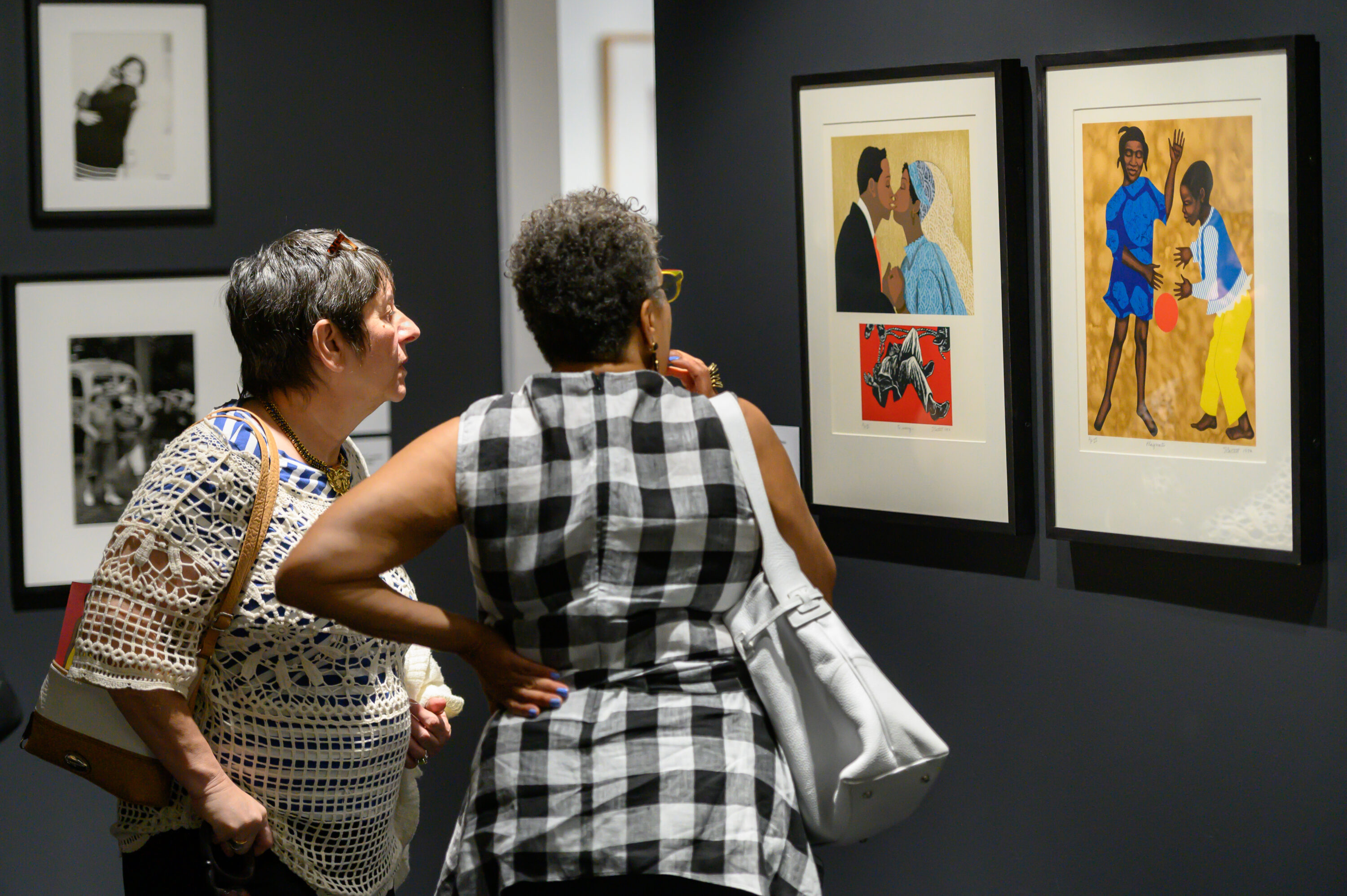 A light-skinned older woman with a cropped hair cut and a dark-skinned older woman also with a cropped hair cut stand in a gallery looking at two colorful lithographs framed side-by-side on a dark grey wall. The artwork on the left shows a dark-skinned couple mid-kiss after getting married; the artwork on the right shows a dark-skinned girl and boy playing with an orange ball.