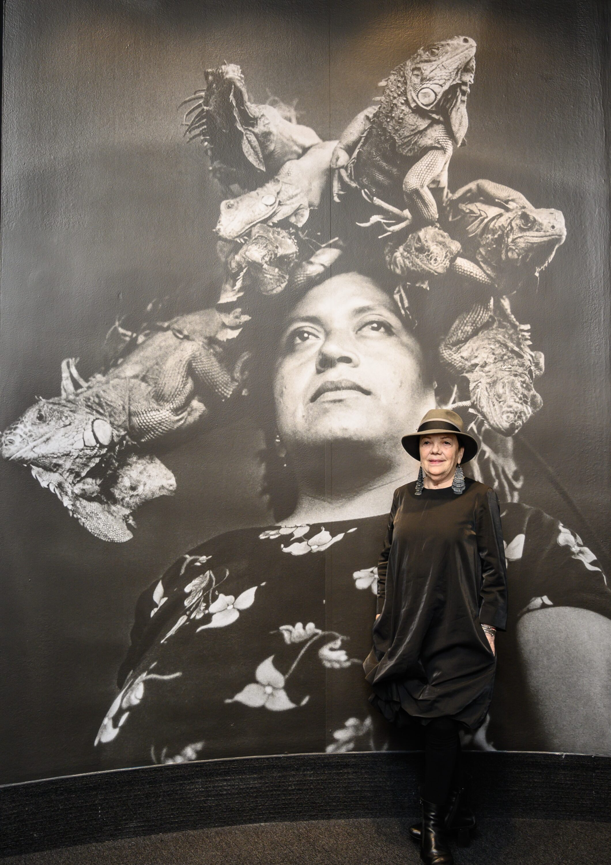 A light-skinned woman wearing a brimmed hat, geometric earrings, and a long-sleeved black velvet dress stands in front of a wall-sized black and white portrait of a woman, who has eight iguanas perched on her head like a crown. The photographed woman looks content and confident.