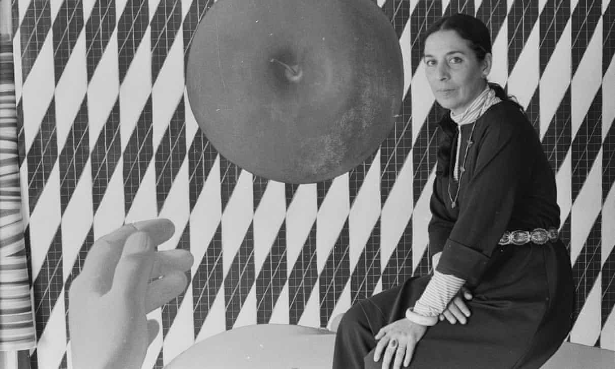 A black-and-white photo of a light-skinned woman sitting in front of a geometric abstract painting that features vertical diamond shaped with a grid-like pattern. A large top-view of an apple is the central focus and a human hand emerges from the bottom of the frame.